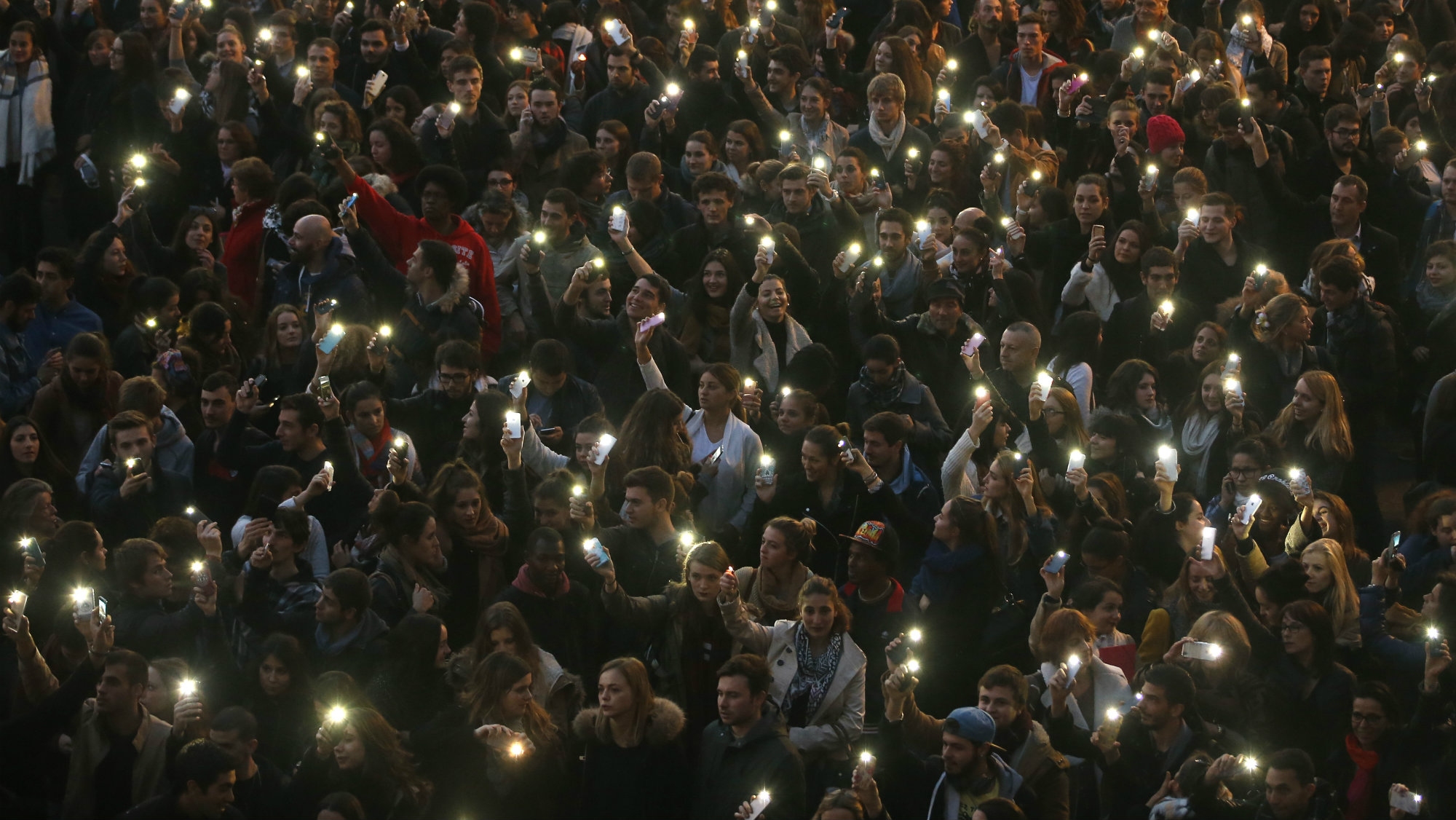 People light their mobile phones during a vigil.