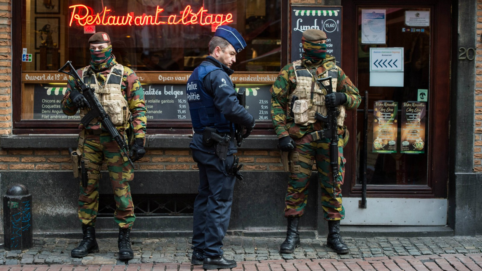 A Police officer and soldiers stand guard in the 'Rue des Bouchers' street, famous for it's restaurants, following the terror alert level being elevated to 4/4, in Brussels, Belgium, 22 November 2015.