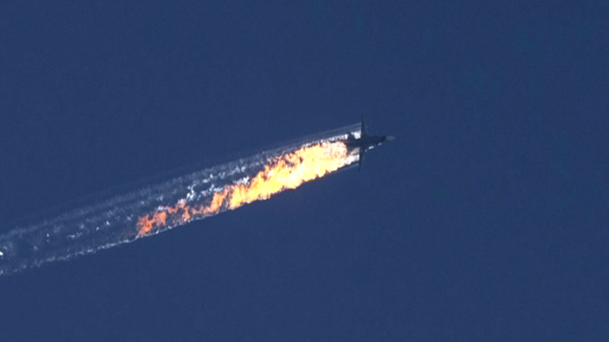 A still image made available on 24 November 2015 from video footage shown by the HaberTurk TV Channel shows a burning trail as a plane comes down after being shot down near the Turkish-Syrian border, over north Syria, 24 November 2015.