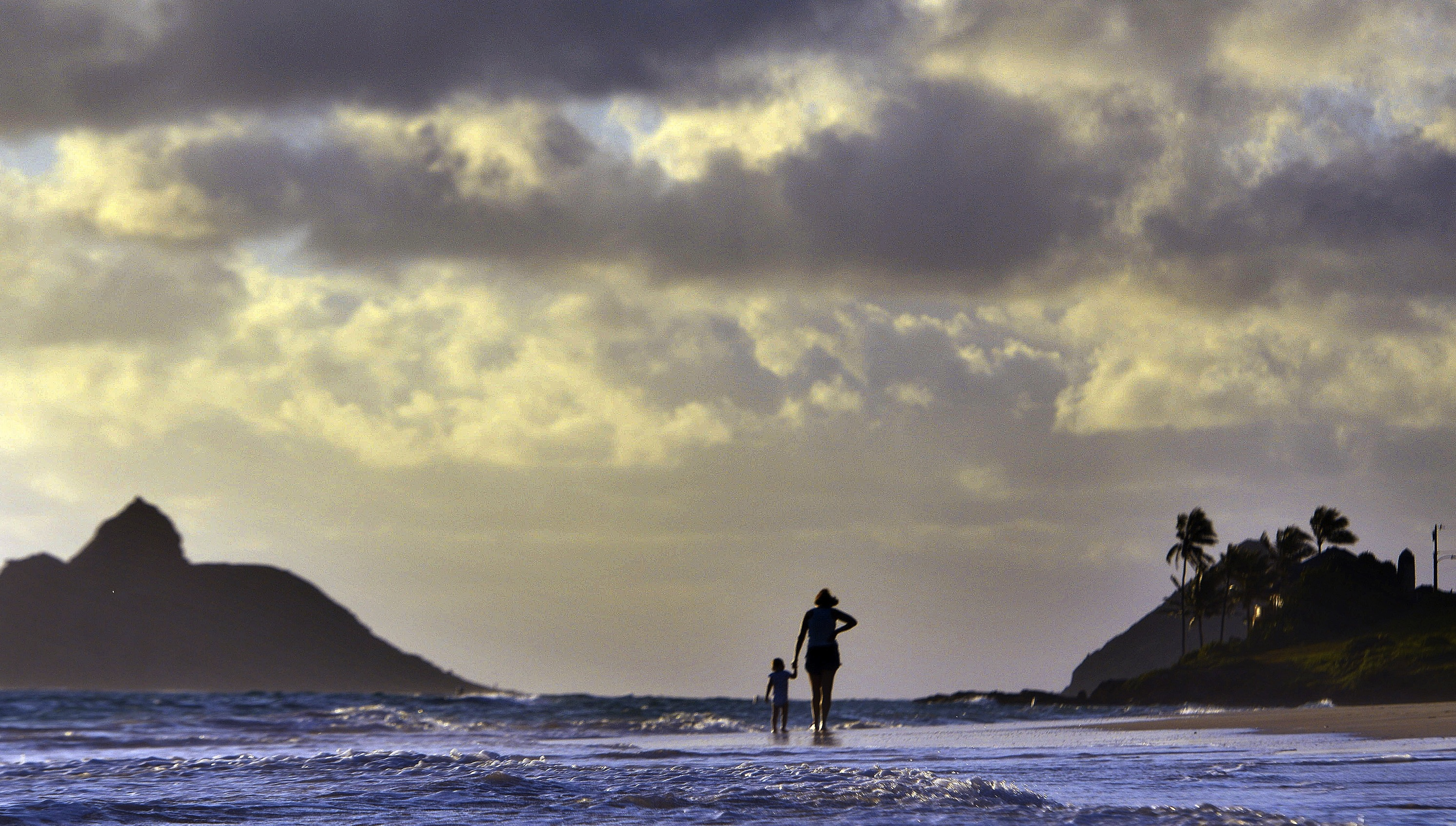Anne Kllingshirn, of Kailua, Hawaii walks with her daughter Emma, 1, as storm clouds float overhead during the sunrise hours on Kailua Beach, in Kailua, Hawaii, Thursday morning Aug. 7, 2014. The National Weather Service downgraded Hurricane Iselle to a tropical storm about 50 miles before it was expected to make landfall early Friday in the southern part of Hawaii's Big Island. By 2 a.m. Hawaii Standard Time on Friday, the storm was swirling about 10 miles from the Kau coastline. (AP Photo/Luci Pemoni