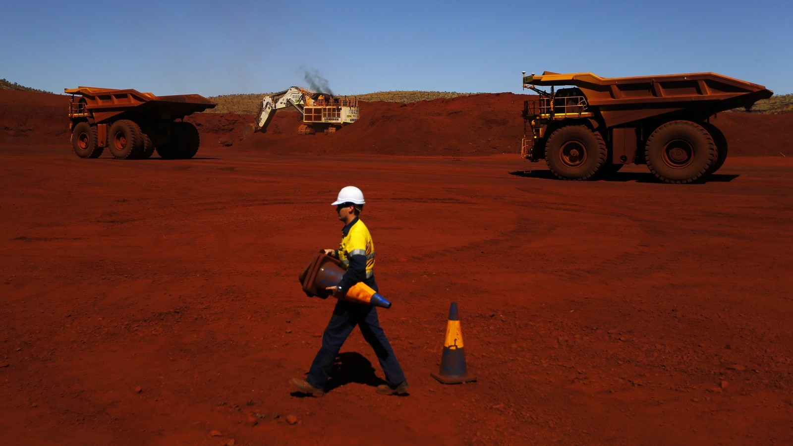 A mine worker lays out safety cones in front of giant mining trucks at the Fortescue Solomon iron ore mine located in the Sheila Valley, around 400 km (249 miles) south of Port Hedland, in the Pilbara region of Western Australia December 2, 2013. Miner Fortescue Metals Group Ltd, which holds some of the world's biggest reserves of iron ore, will call a temporary end to growth next year until it pays off billions of dollars in debt used to fund massive expansion work. To match Interview AUSTRALIA-FORTESCUE/ REUTERS/David Gray (AUSTRALIA - Tags: BUSINESS COMMODITIES) - RTX161CB