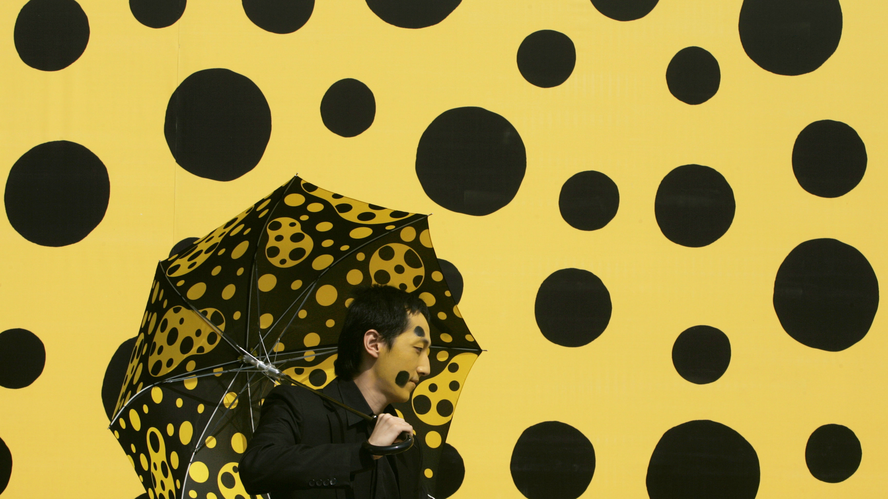 """A dancer performs in front of a backdrop marking the opening of """"Dots Obsession: Soul of Pumpkin"""", an installation art exhibition by Japanese artist Yayoi Kusama, in Hong Kong October 9, 2007. REUTERS/Bobby Yip (CHINA)"""