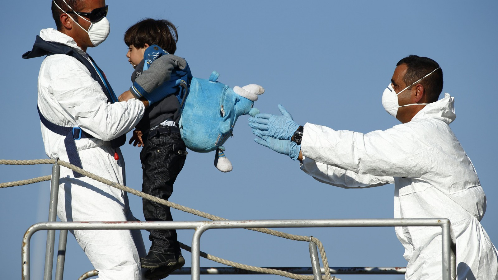 Armed Forces of Malta (AFM) sailors disembark a would-be immigrant child.