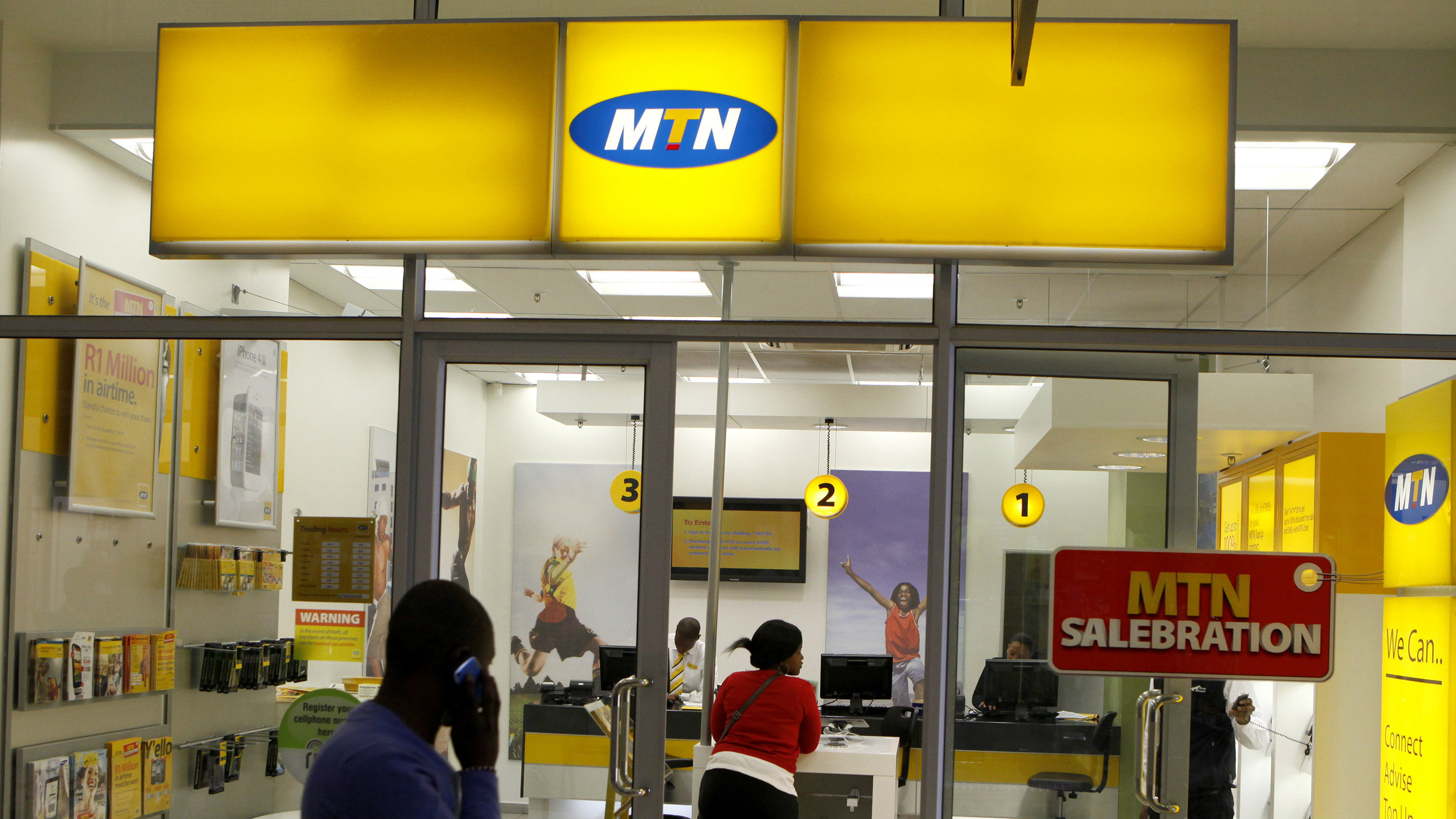 A man speaks on a mobile phone as he walks past a MTN shop at a shopping mall south of Johannesburg June 6, 2012.