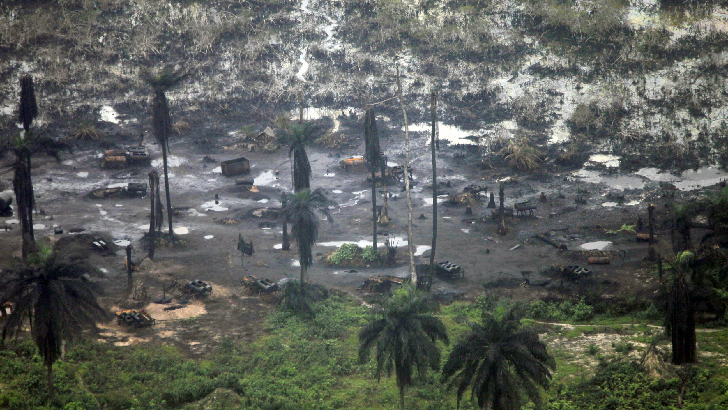 """A view of an illegal oil refinery is seen in Ogoniland outside Port Harcourt in Nigeria's Delta region March 24, 2011.Crude oil thieves -- known locally as """"bunkerers"""" -- have been a fact of life for years in Africa's biggest oil and gas industry, puncturing pipelines and costing Nigeria and foreign oil firms millions of dollars in lost revenues each year. REUTERS/Akintunde Akinleye (NIGERIA - Tags: CRIME LAW ENERGY)"""