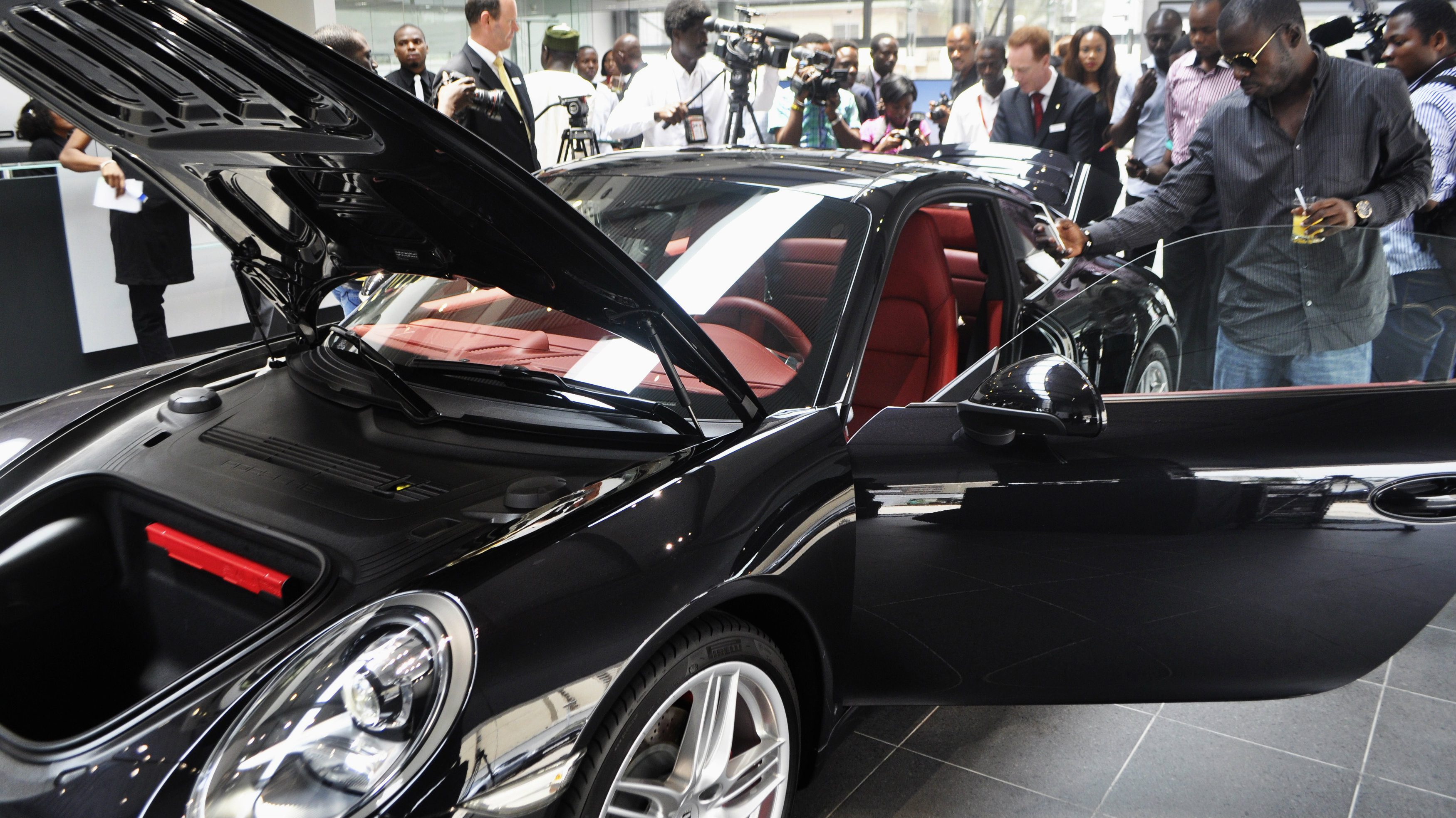 Nigerians look at a vehicle by German carmaker Porsche in Lagos March 14, 2012. Porsche officially opened a new car dealership on March 16 in the heart of Lagos' wealthiest district, Victoria Island, a place with one of the world's highest concentrations of millionaires. High-end goods producers are increasingly targeting sub-Saharan Africa, as its economic growth starts to dwarf other continents. As rich Western countries face a slowdown, sub-Saharan African economies are expected to see growth of six percent on average in 2012, according to the IMF. Nigeria, Africa's second biggest economy, grew 7.68 percent in the last quarter of 2011, one of the fastest in the world. Picture taken March 14, 2012. REUTERS/Monica Mark (NIGERIA - Tags: TRANSPORT BUSINESS SOCIETY)