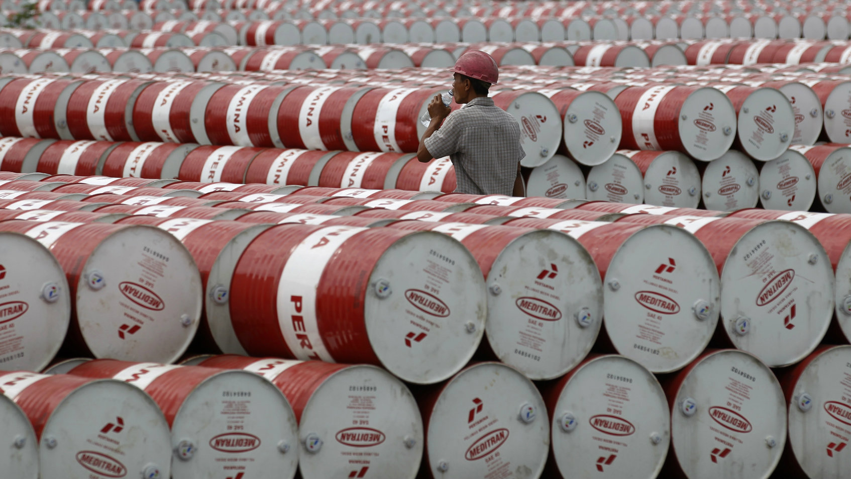 A worker walks in between oil barrels in Jakarta, Indonesia.