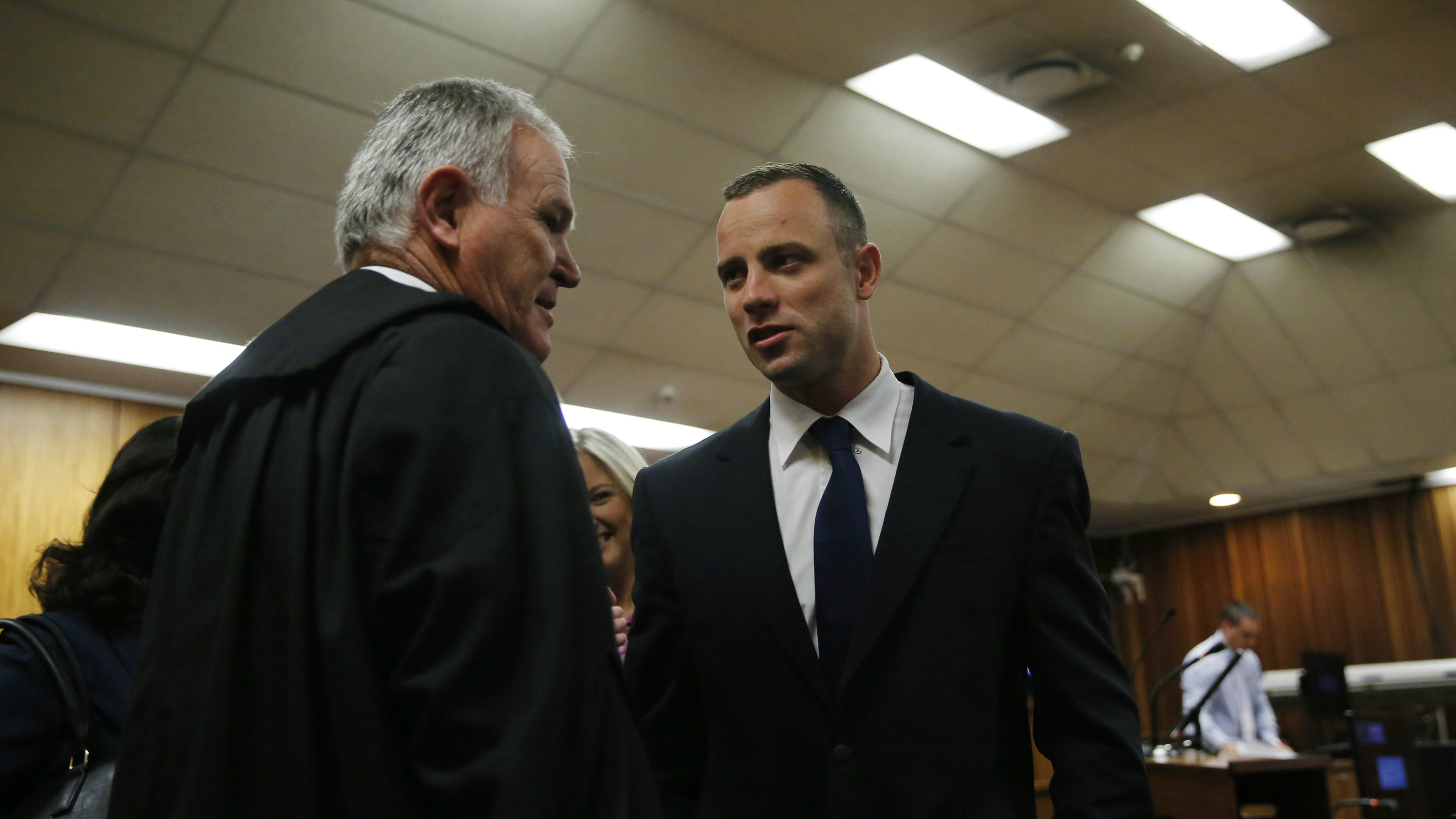 Oscar Pistorius, right, talks with his defense attorney Barry Roux, left, in a courtroom at the high court in Pretoria, South Africa, Tuesday, May 6, 2014. A man who lives next to the house where Pistorius fatally shot his girlfriend has testified at the athlete's murder trial about the night of the killing, saying he heard a man crying loudly and that he called the security of the housing estate for help. (AP Photo/Mike Hutchings, Pool)