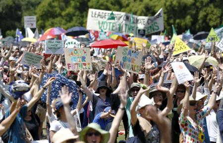 Protesters raise their hands in Sydney, Australia.
