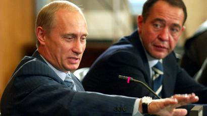 Russian President Vladimir Putin (L) gestures as Mass Media Minister Mikhail Lesin listens to him during a meeting with local press in the far eastern city of Vladivostok, August 24, 2002. President Vladimir Putin pressed North Korea on Friday to forge a new Asia-Europe freight route by extending Russia's trans-Siberian railway across the Korean peninsula to bypass China.
