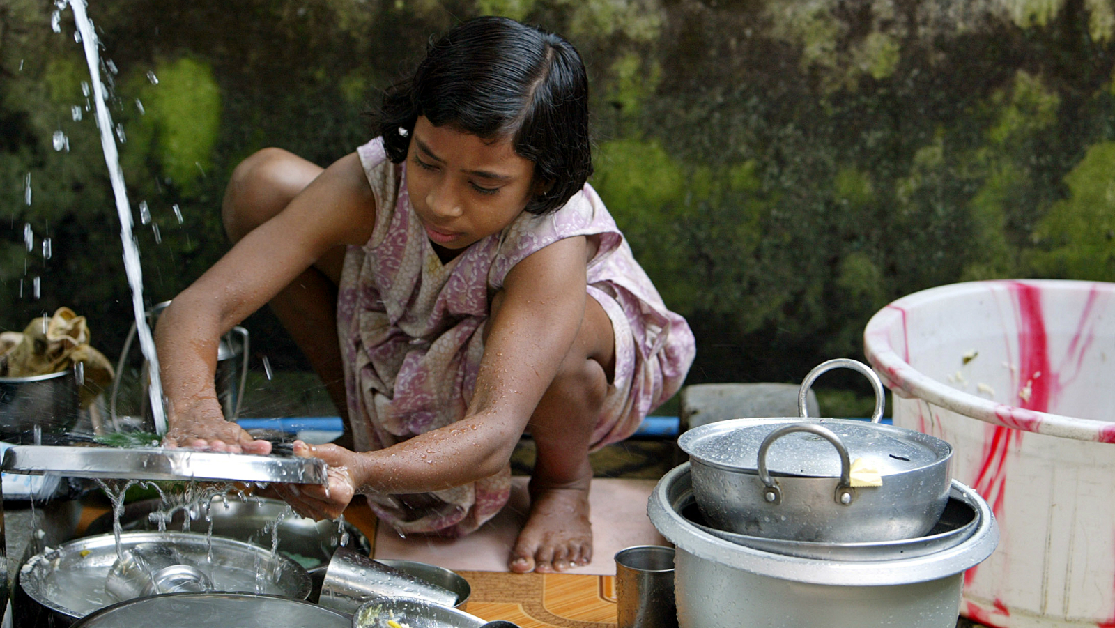 Sumana Barman, 11, a child labourer washes utensils at a house in the northeastern Indian city of Siliguri October 13, 2006.