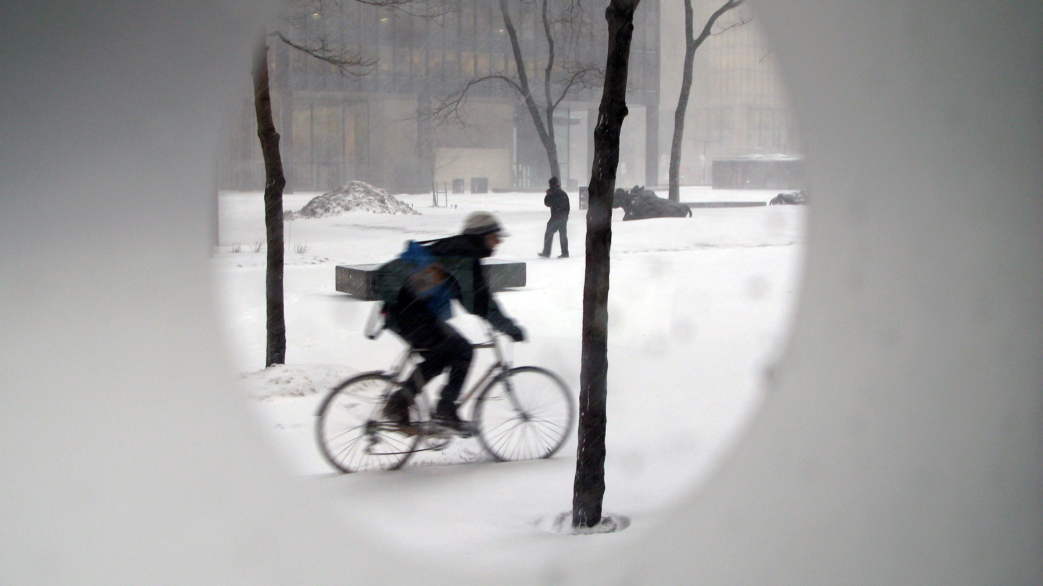 A bicycle courier cycles through a building courtyard during a snowstorm in Toronto, March 1, 2007.