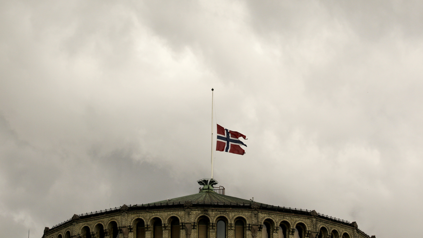 The Norwegian flag flutters at half-mast on the roof of the parliament building in Oslo July 23, 2011. Norwegian police searched for more victims on Saturday after a suspected right-wing zealot killed at least 92 people in a shooting spree and bomb attack that have traumatised a once-placid country. REUTERS/Wolfgang Rattay (NORWAY - Tags: CIVIL UNREST CRIME LAW IMAGES OF THE DAY) - RTR2P73Q