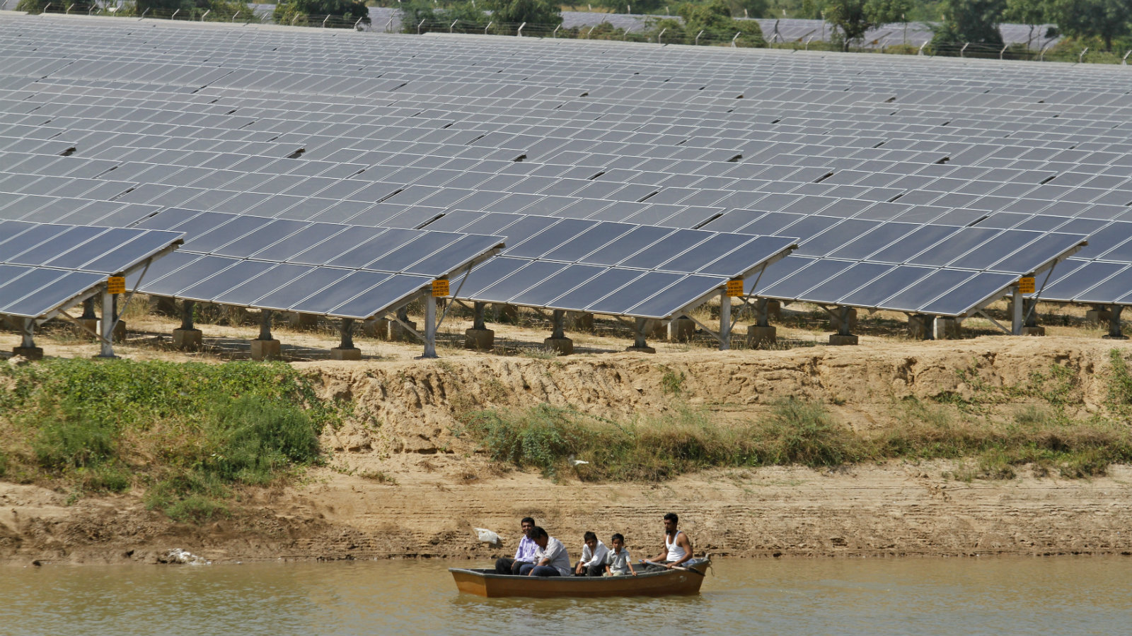 Security personnel sit in a boat as they patrol the premises of a newly inaugurated solar farm at Gunthawada village in Banaskantha district in the western Indian state of Gujarat October 14, 2011. The solar farm is Asia's largest, according to its developer Moser Baer Clean Energy. It is spread over an area of 305 acres and is expected to generate 52 million kilowatt hours of energy annually.