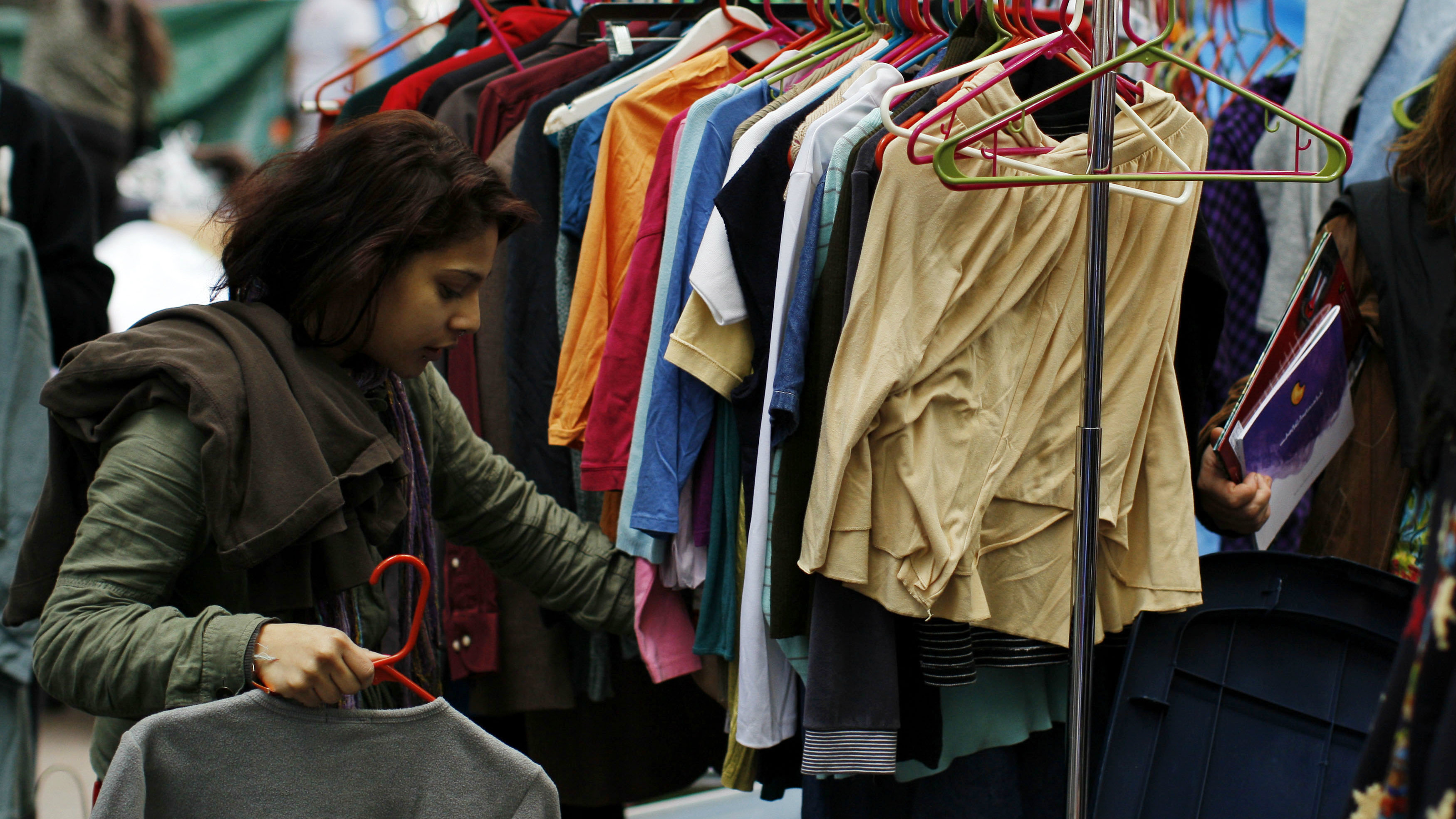 A member of the Occupy Wall Street movement picks up clean clothes from a rack of free donated clothes...