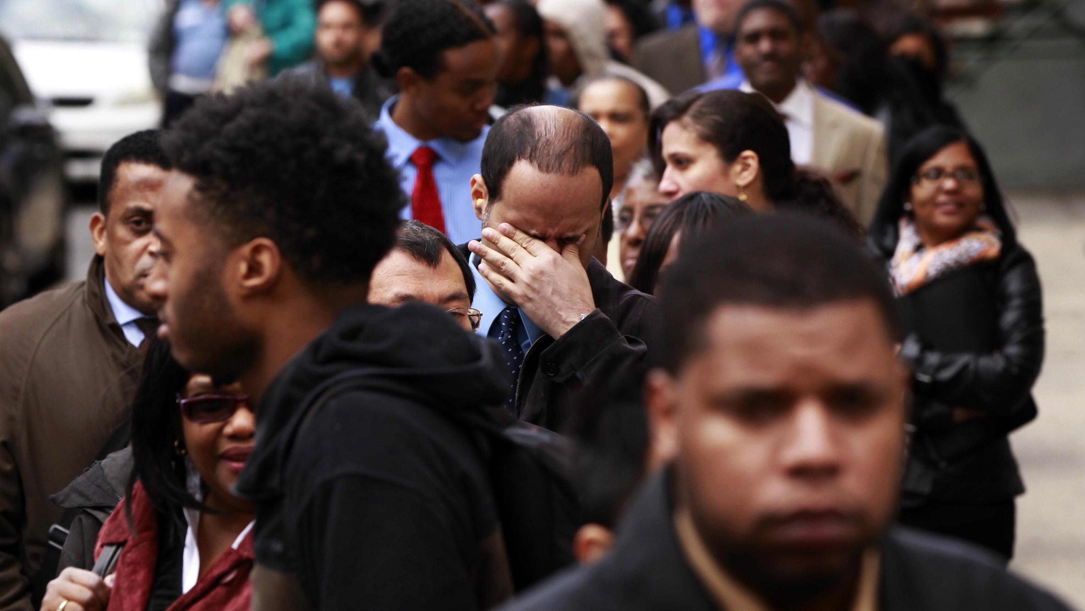 A man rubs his eyes as he waits in a line of jobseekers.