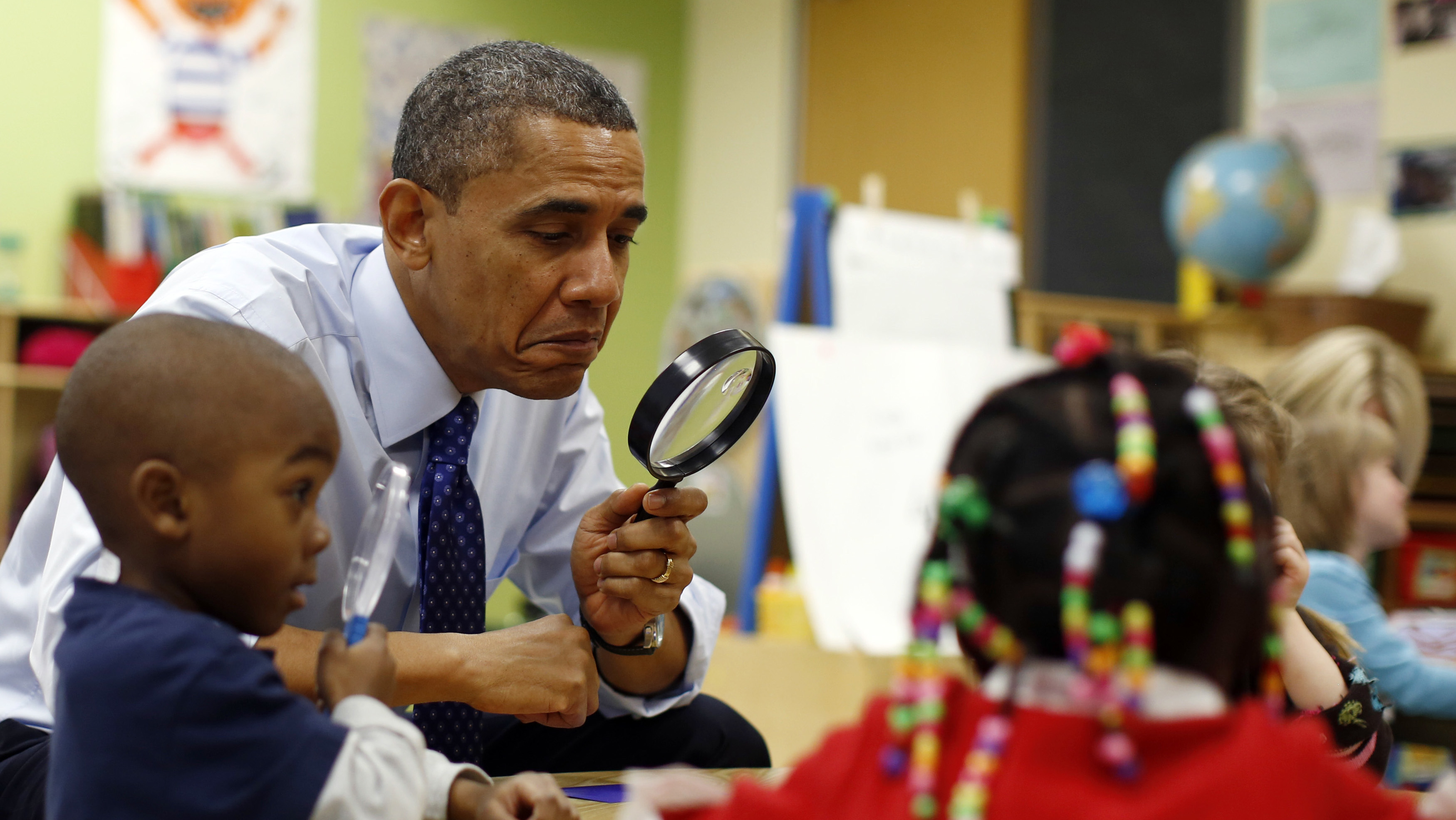 Obama uses a magnifying glass to play a game with children in a pre-kindergarten classroom at College Heights early childhood learning center in Decatur