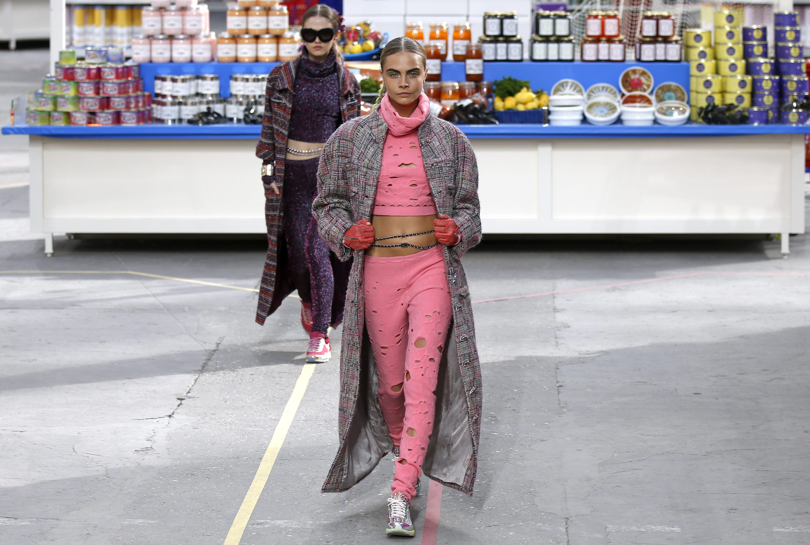 """Model Cara Delevingne presents a creation by German designer Karl Lagerfeld as part of his Fall/Winter 2014-2015 women's ready-to-wear collection for French fashion house Chanel at the Grand Palais transformed into a """"Chanel Shopping Center"""" during Paris Fashion Week March 4, 2014."""