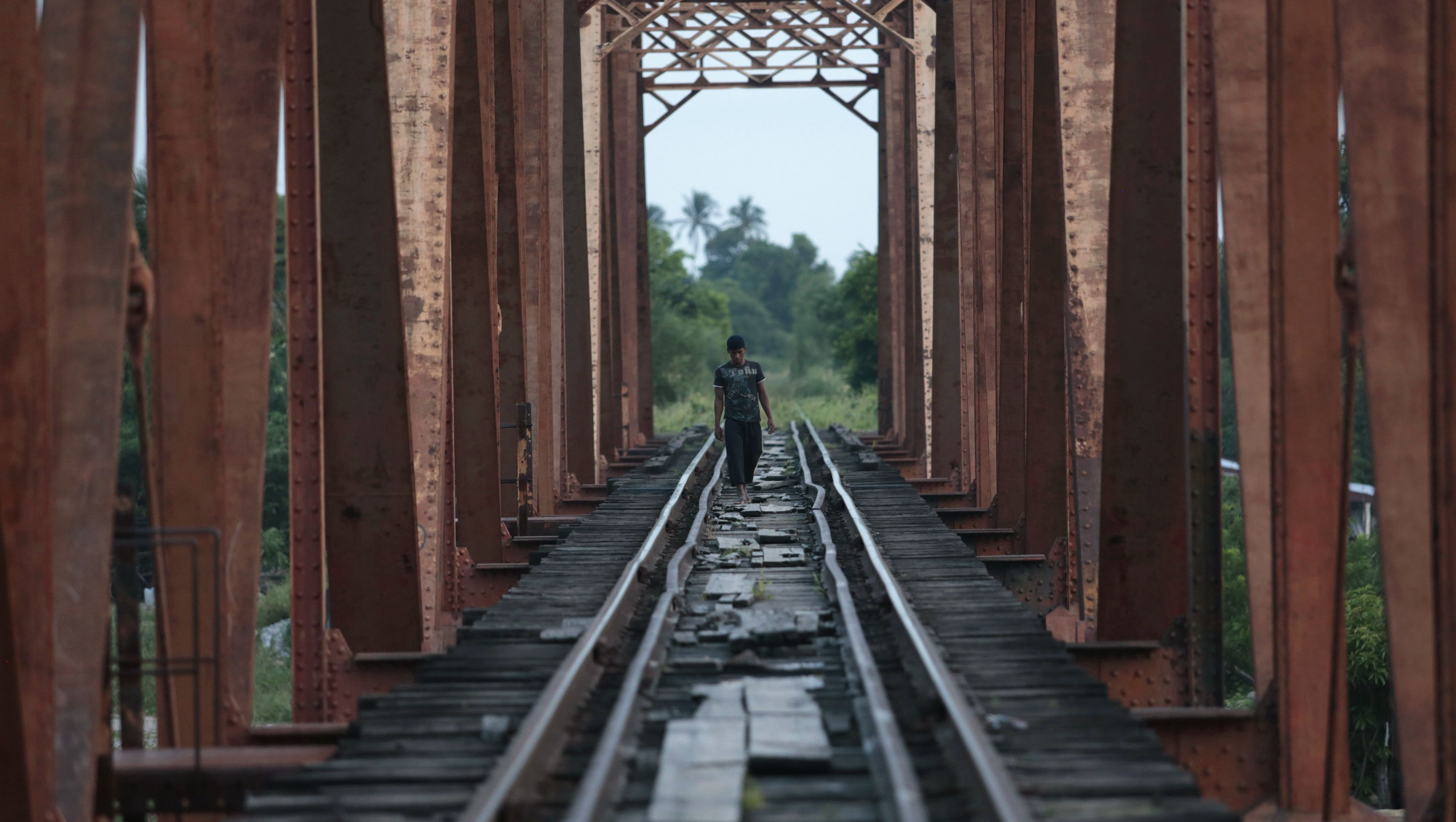 Central American migrant walks on the train tracks in Arriaga
