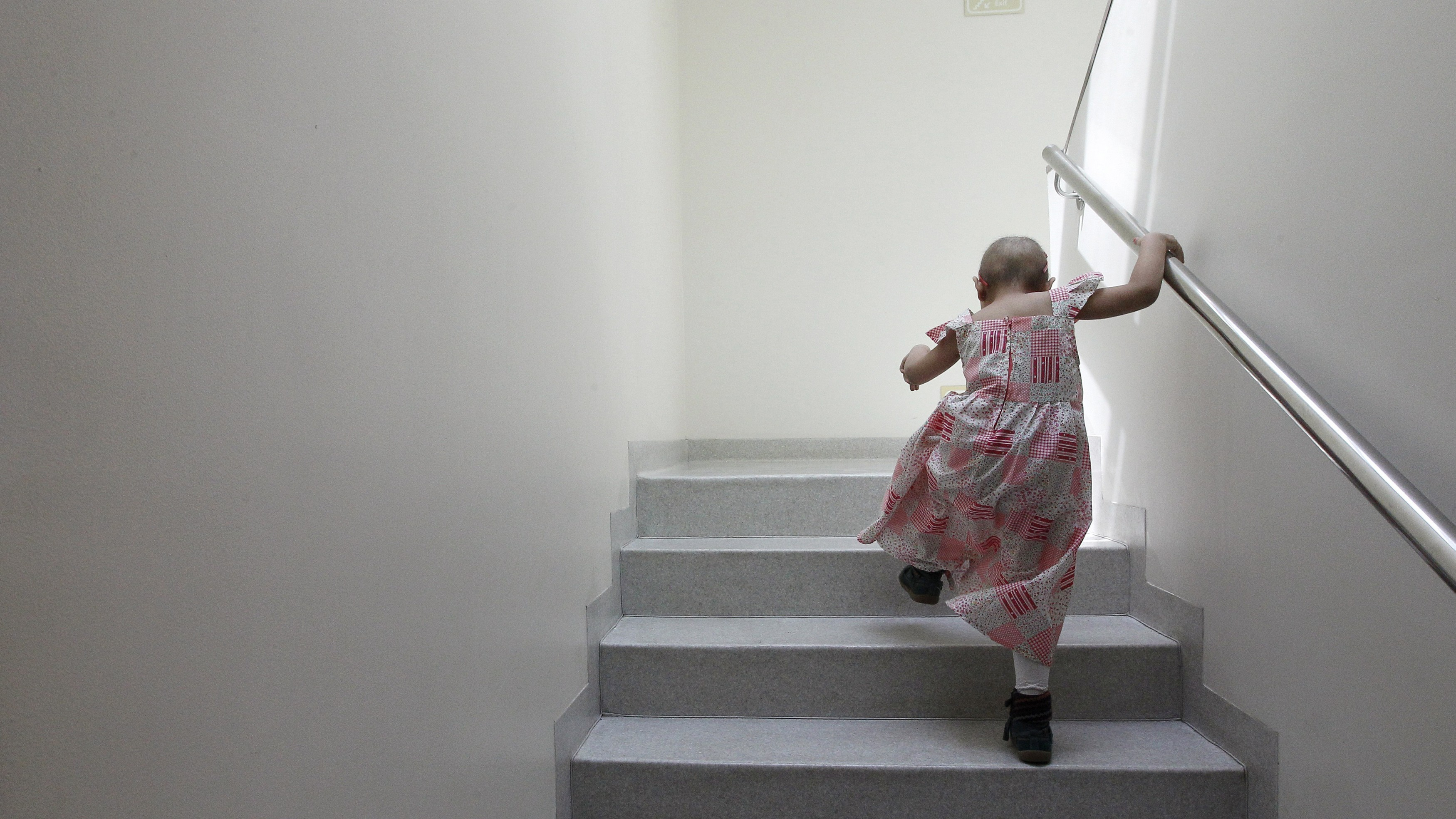A child with hair loss from cancer treatment climbs a set of stairs