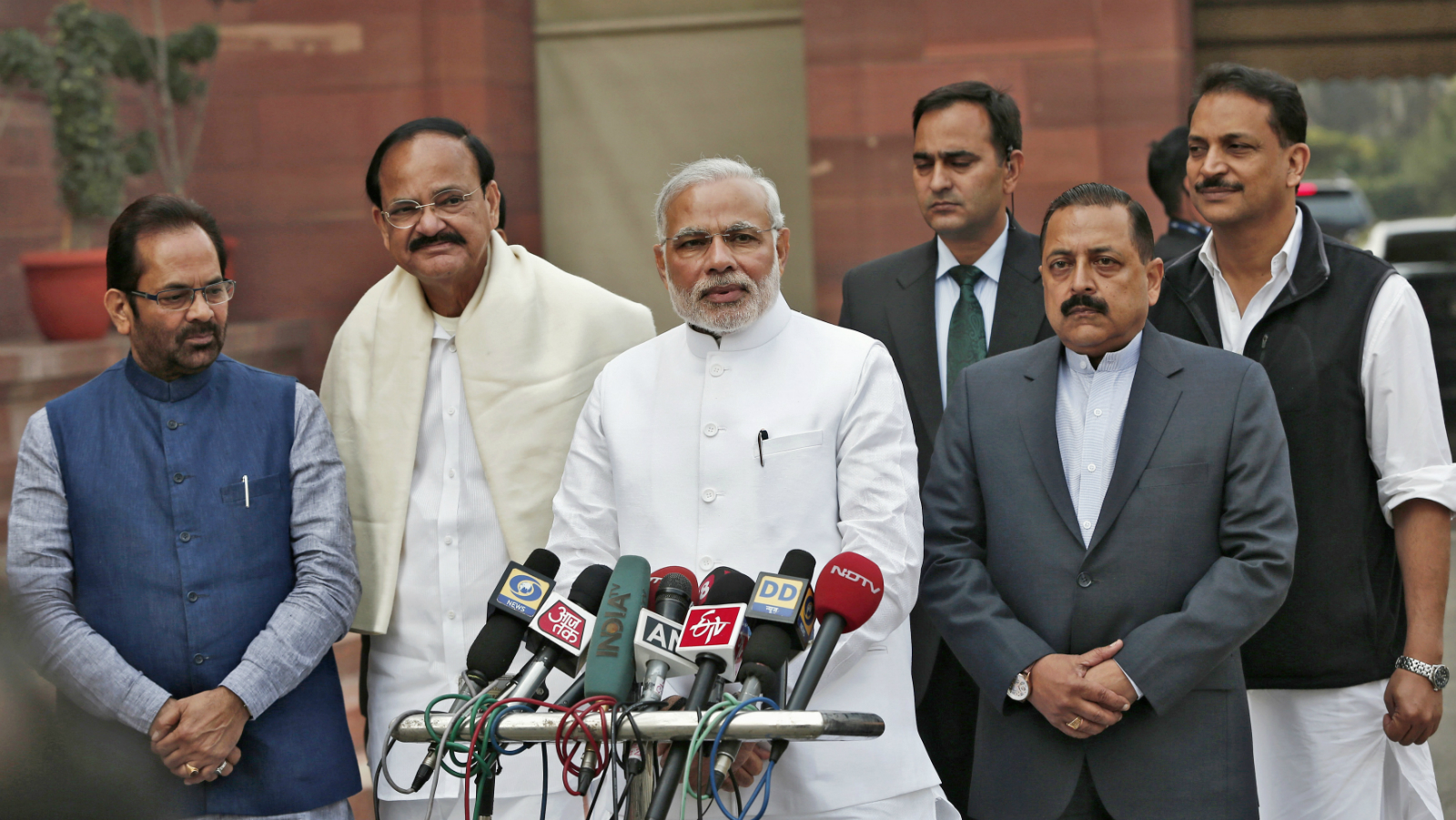 India's Prime Minister Narendra Modi (3rd L) speaks to the media as Minister of State for Parliamentary Affairs Mukhtar Abbas Naqvi (L), Venkaiah Naidu (2nd L), Minister of Urban Development, Jitendra Singh (2nd R), Minister of State for Prime Minister Office, and Rajiv Pratap Rudy (R), Minister of State for Skill Development and Entrepreneurship, look on upon arrival on the opening day of the winter session of the Indian Parliament in New Delhi November 24, 2014.