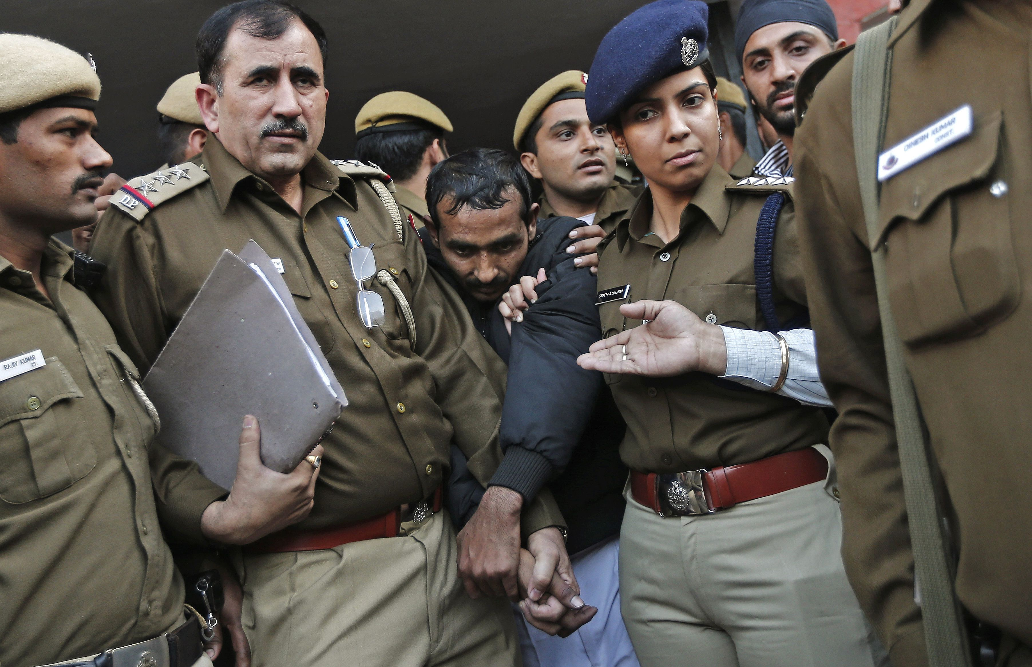 Policemen escort driver Shiv Kumar Yadav (C in black jacket) who is accused of a rape outside a court in New Delhi December 8, 2014. U.S. online ride-hailing service Uber has been banned from operating in the Indian capital after a female passenger accused one of its drivers of rape, a case that has reignited a debate about the safety of women in the South Asian nation.  REUTERS/Adnan Abidi (INDIA - Tags: CRIME LAW BUSINESS TRANSPORT TPX IMAGES OF THE DAY) - RTR4H45S