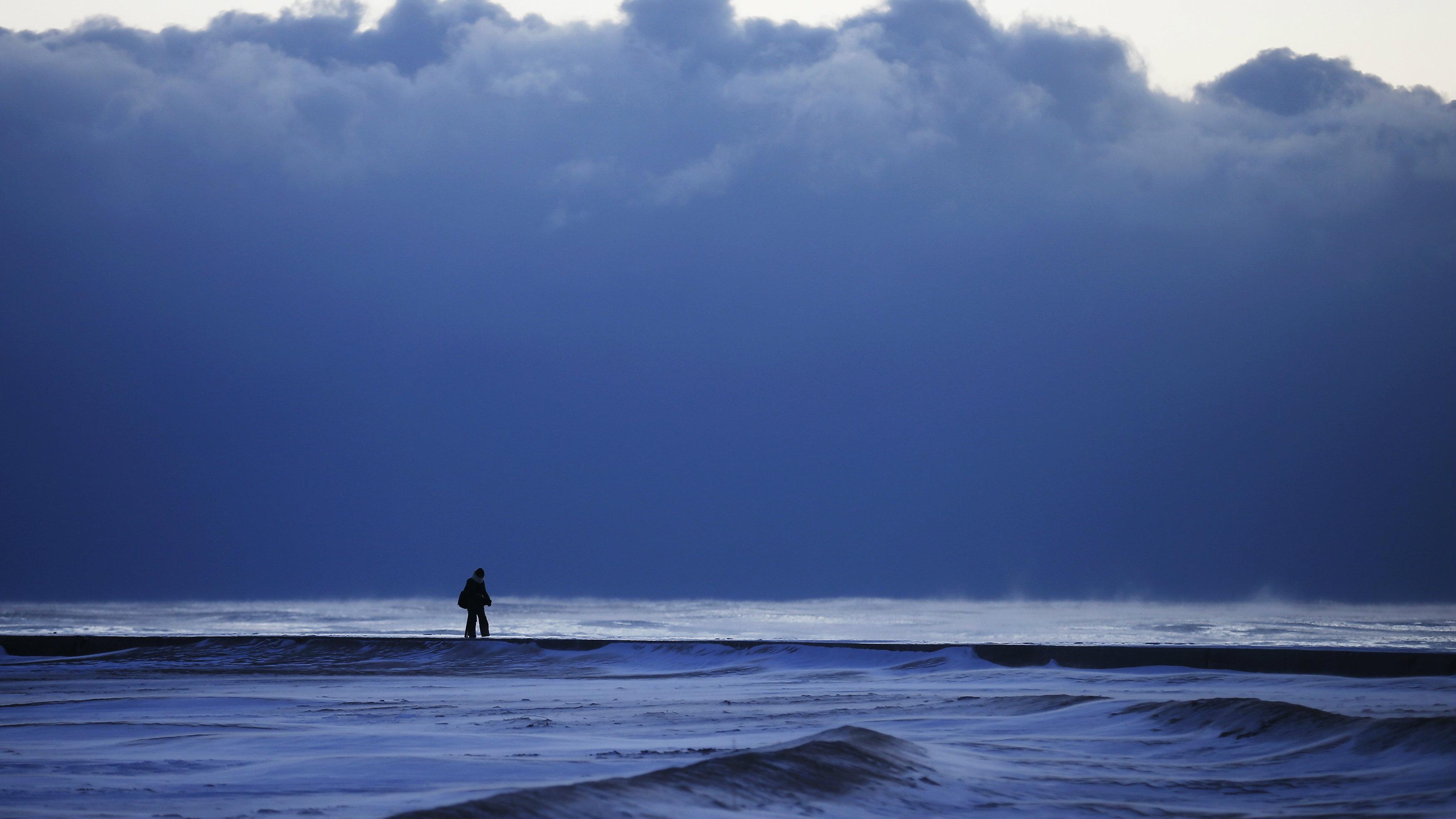 A woman walks along a frozen beach at Lake Michigan in Chicago.
