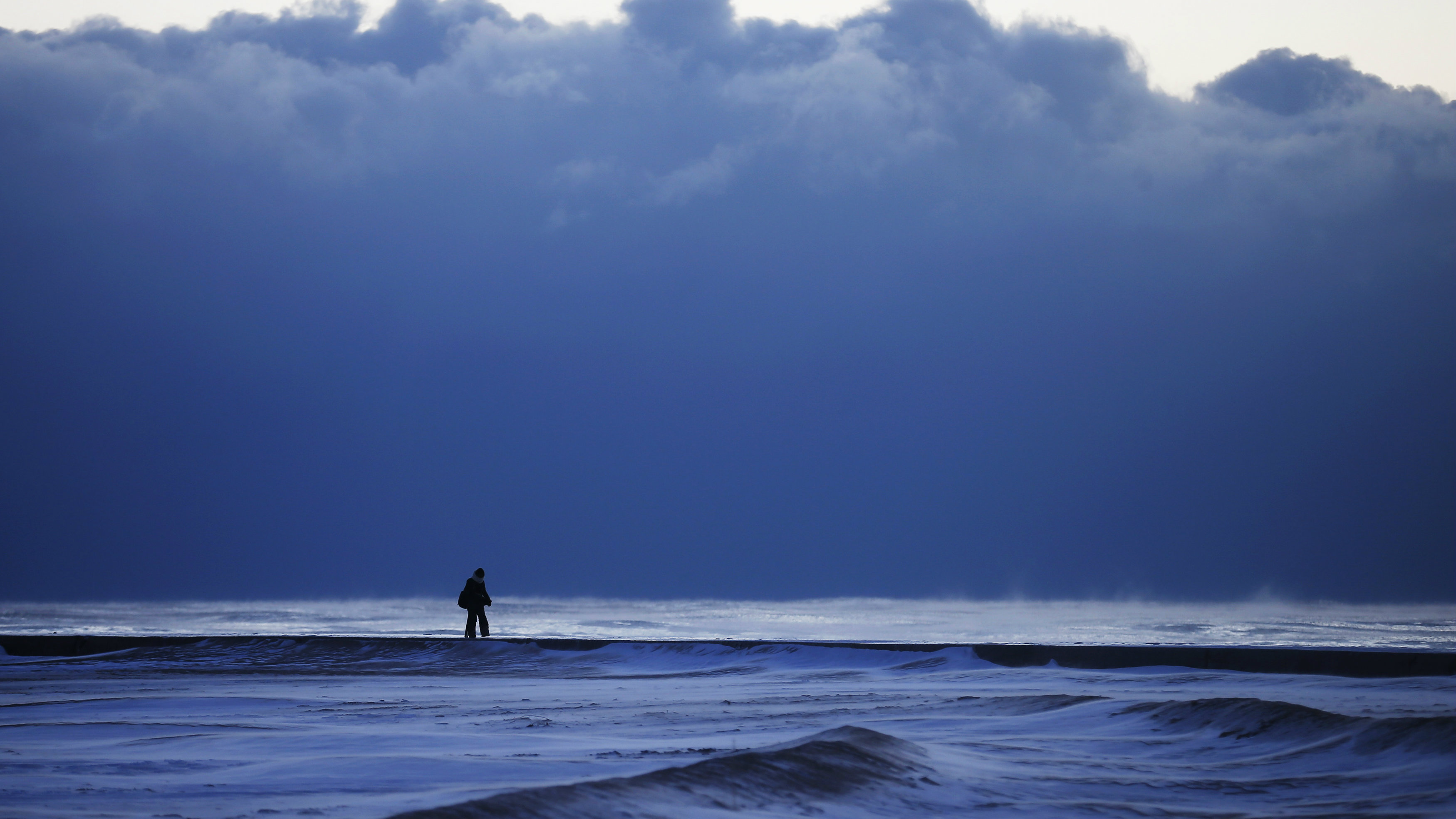 A woman walks along a frozen beach at Lake Michigan in Chicago.