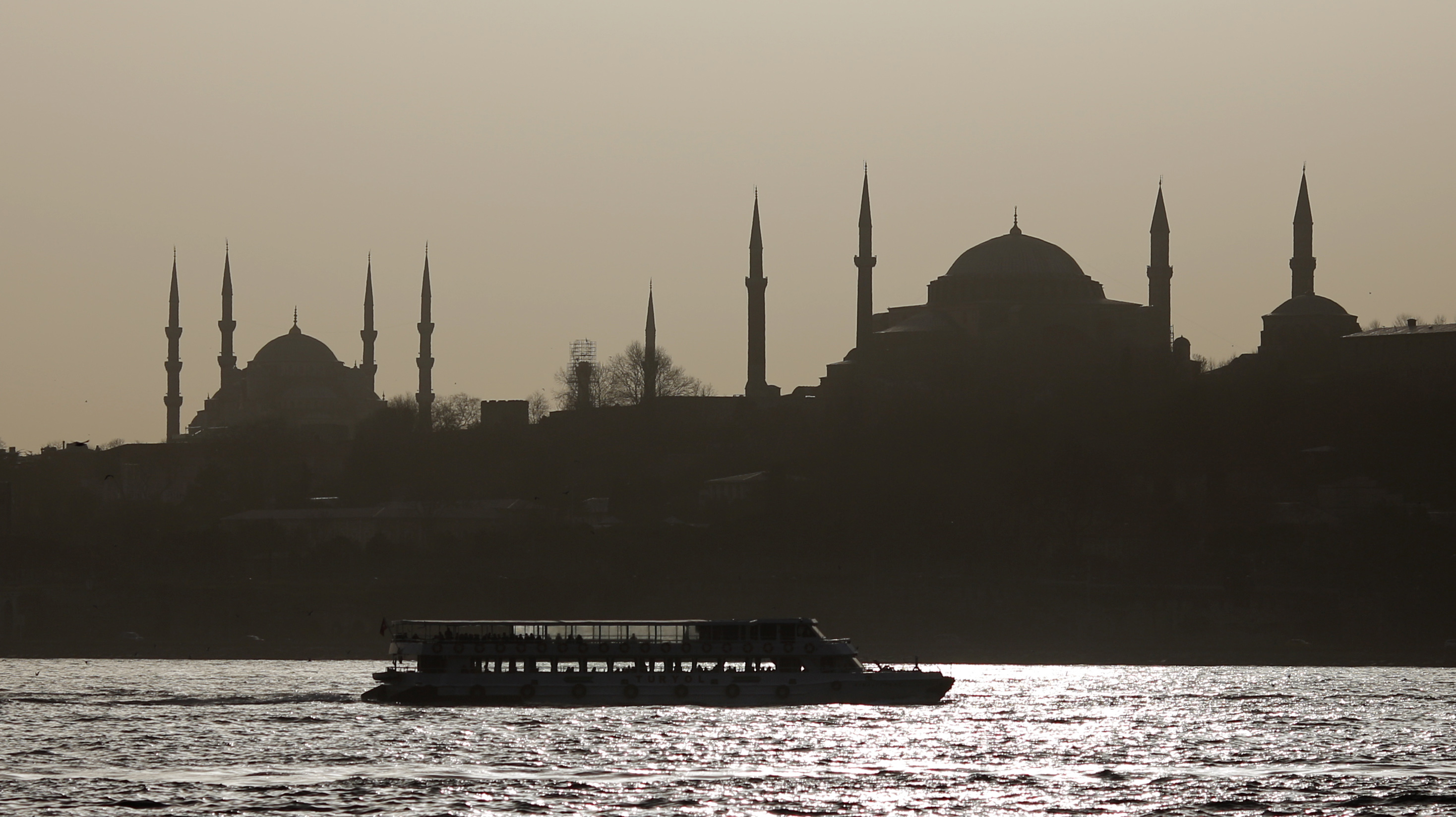 A passenger ferry, with the old city's monuments Blue mosque and Hagia Sophia museum in the background, sets sail in the Bosphorus in Istanbul