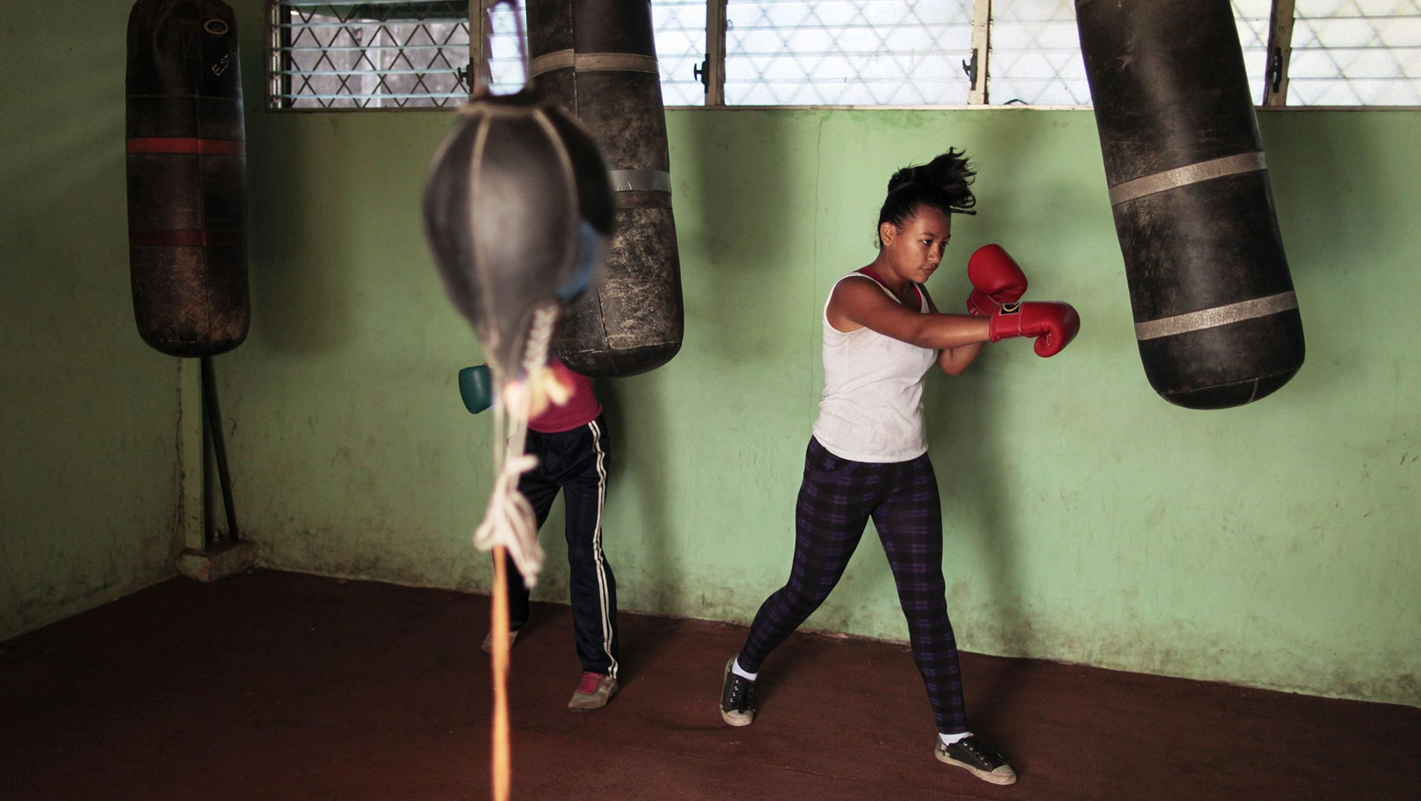 A woman trains with a punch bag at the National Institute of Sport in Managua