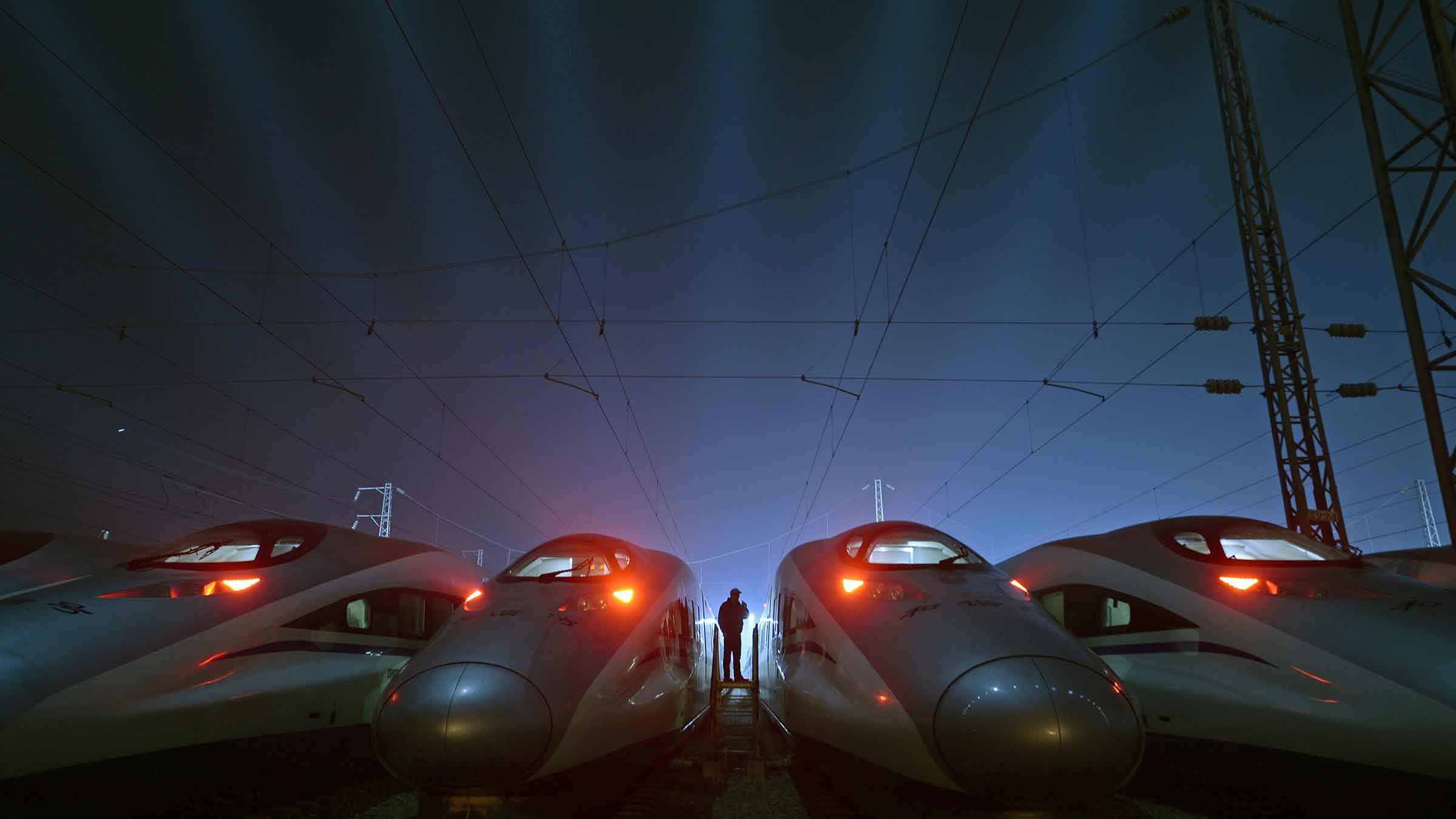 A worker stands among CRH Harmony bullet trains at a high-speed train maintenance base in Wuhan