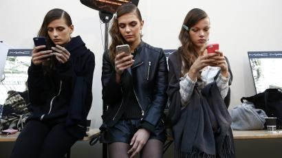 Models look at their mobile phones backstage before the Guy Laroche Spring/Summer 2016 women's ready-to-wear...
