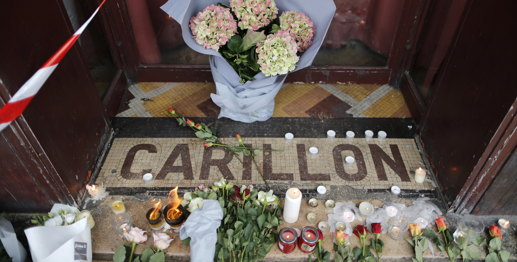 Flowers are seen placed on the doorstep of the Le Carillon restaurant the morning after a series of deadly attacks in Paris , November 14, 2015.      REUTERS/Christian Hartmann - RTS6ZE8
