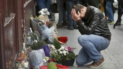 A man pays his respect outside the Le Carillon restaurant the morning after a series of deadly attacks in Paris.