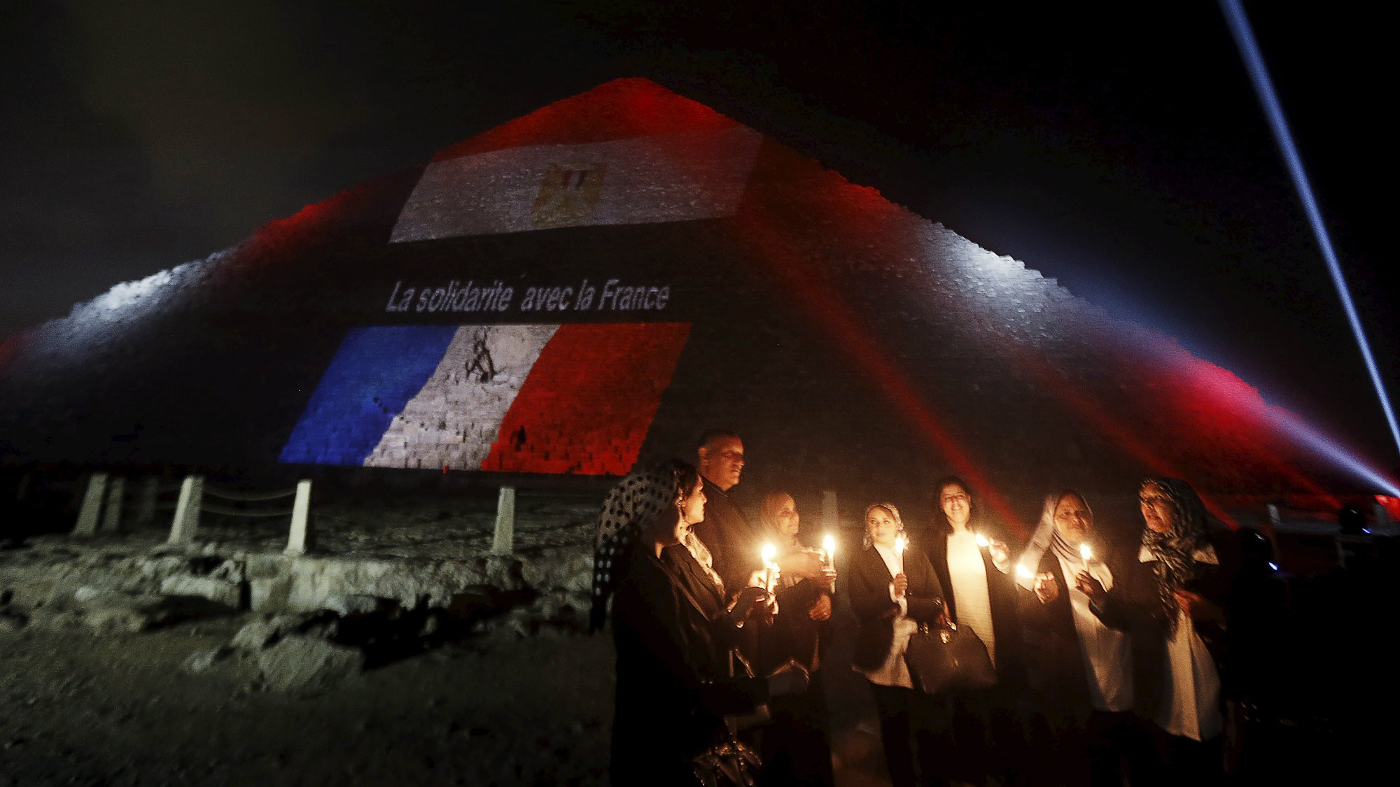 Egyptians light candles as the French and Egyptian flags and France's national colors of blue, white and red are projected onto one of the Giza pyramids, in tribute to the victims of the Paris attacks, on the outskirts of Cairo, Egypt, November 15, 2015.