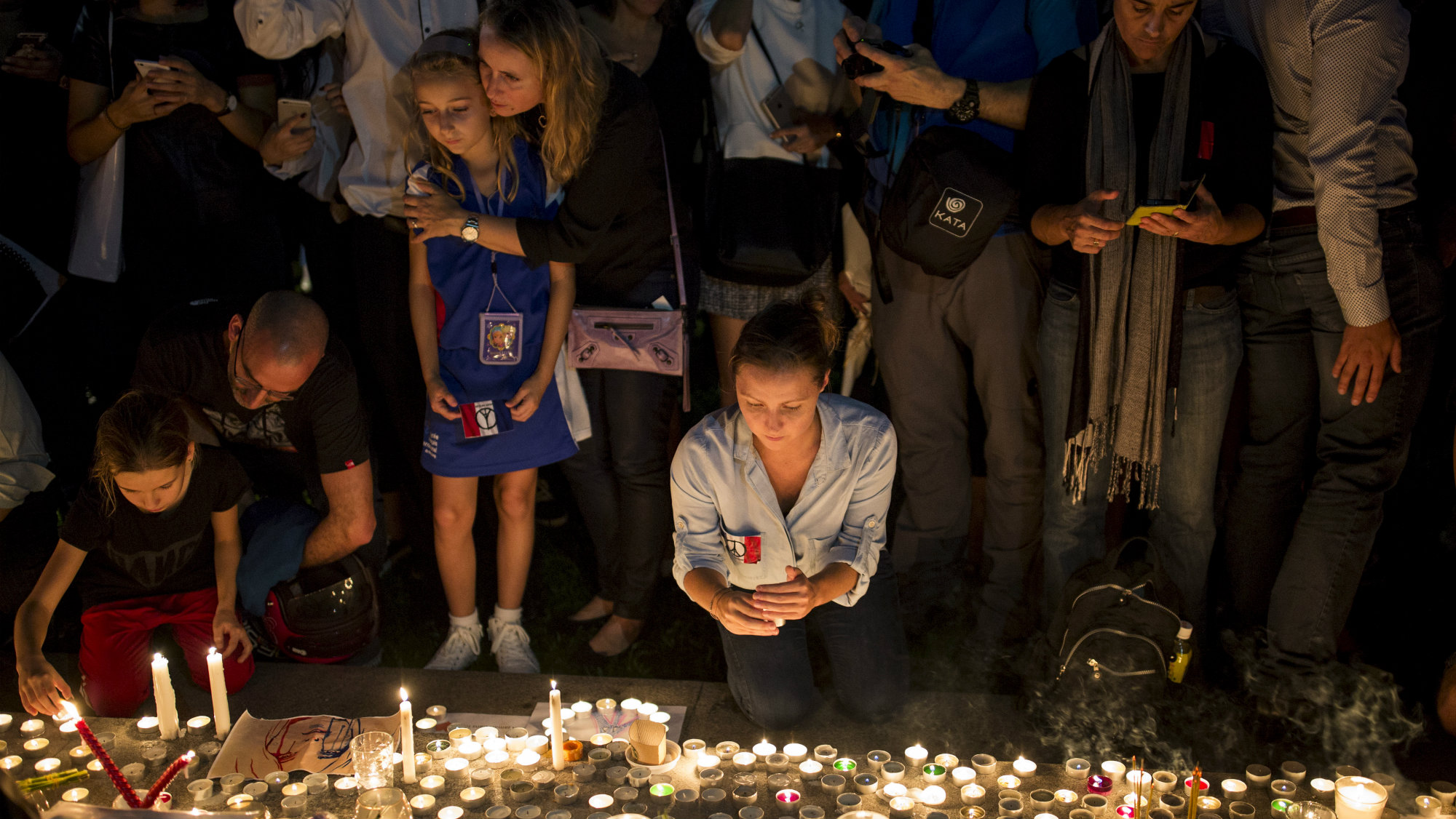 People light candles during a vigil for the victims of the Paris attacks.