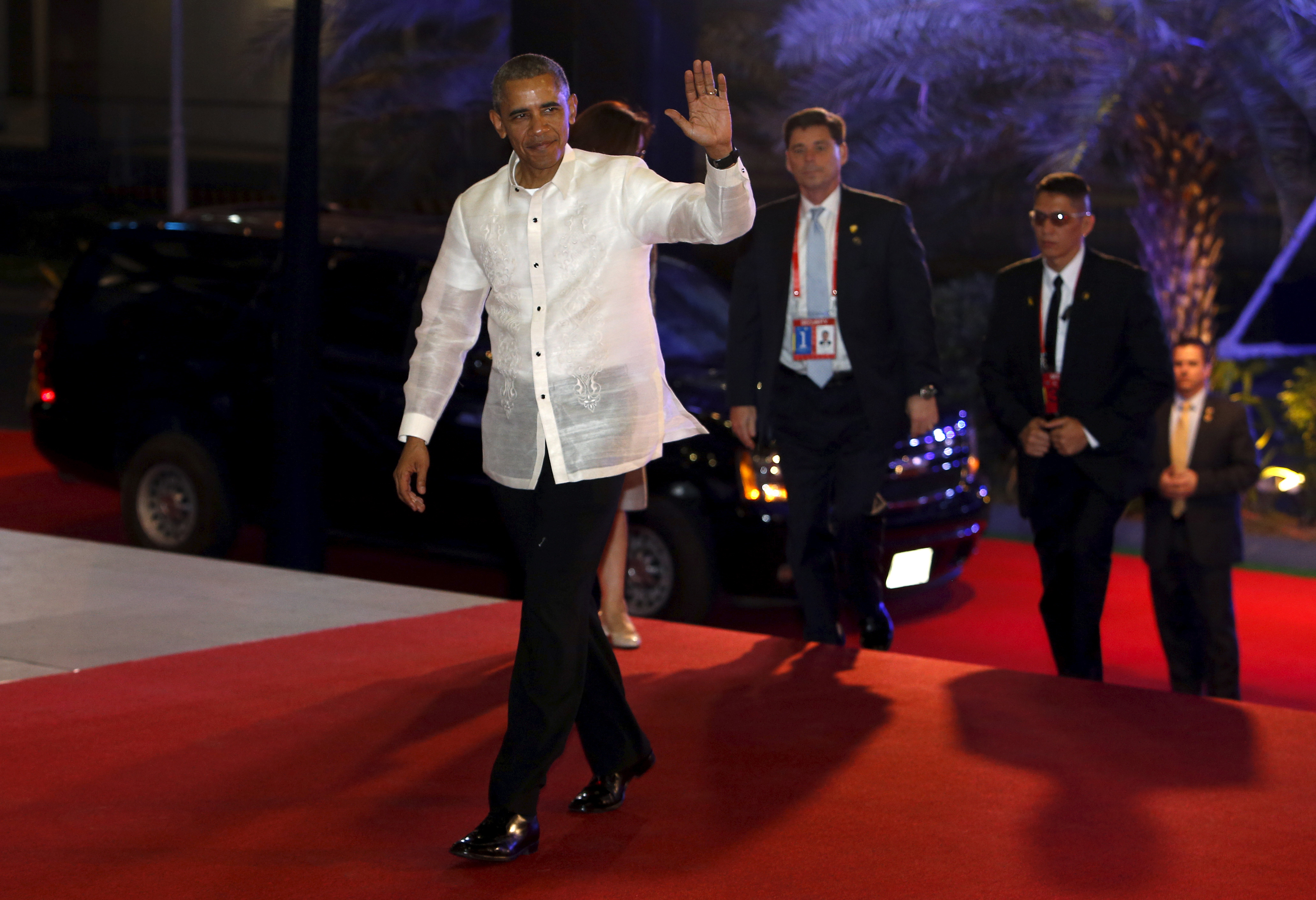 "U.S. President Barack Obama, wearing the traditional Philippine ""barong"" shirt, waves as he arrives for a welcome dinner during the Asia-Pacific Economic Cooperation (APEC) summit in the capital city of Manila, Philippines November 18, 2015."