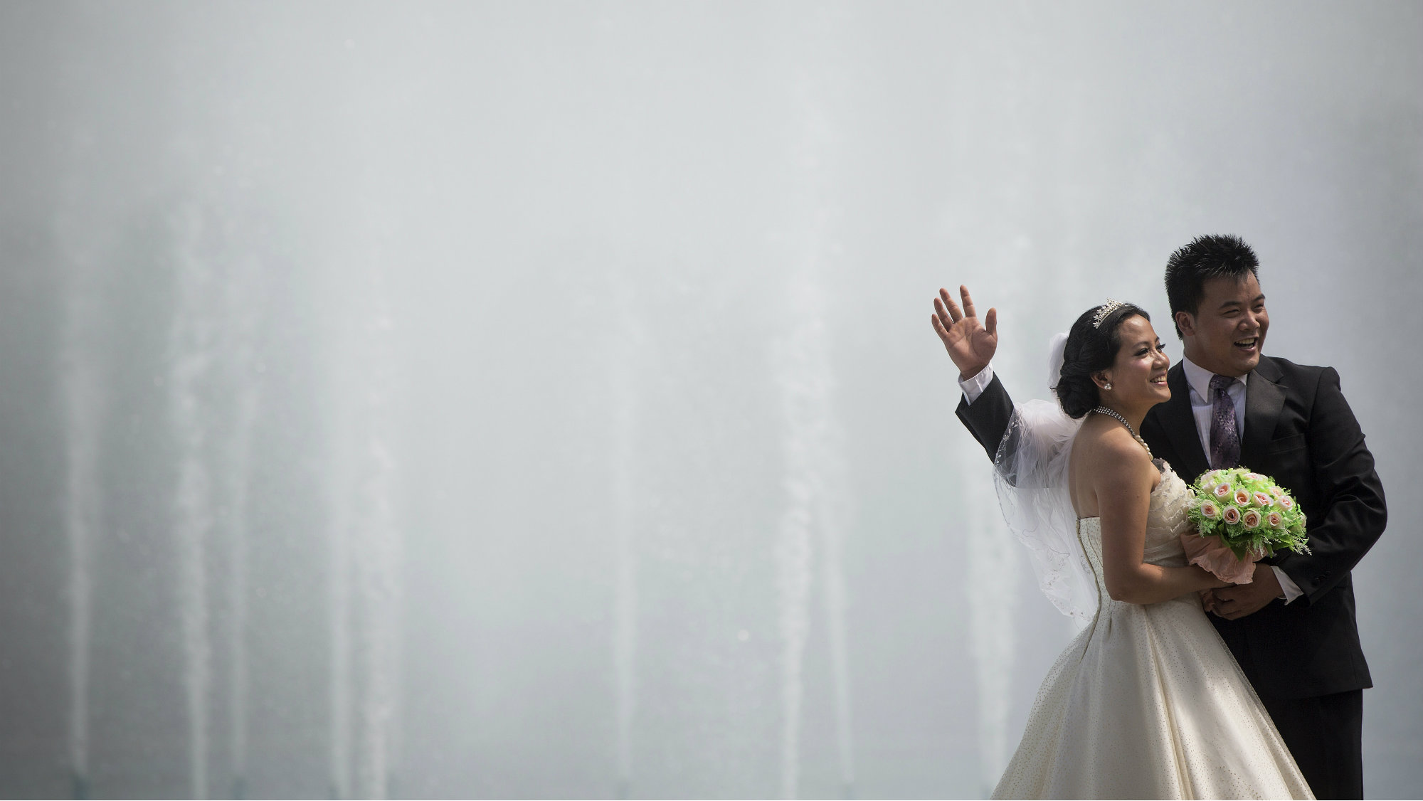 A bride and groom take pictures by the fountains of the Unisphere at Flushing Meadows Corona Park in the borough of Queens in New York July 9, 2013. REUTERS/Shannon Stapleton (UNITED STATES - Tags: SOCIETY ENVIRONMENT)