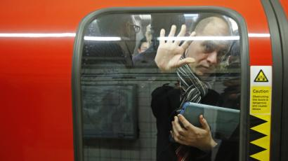 A passenger is squeezed up against a door on the London tube.