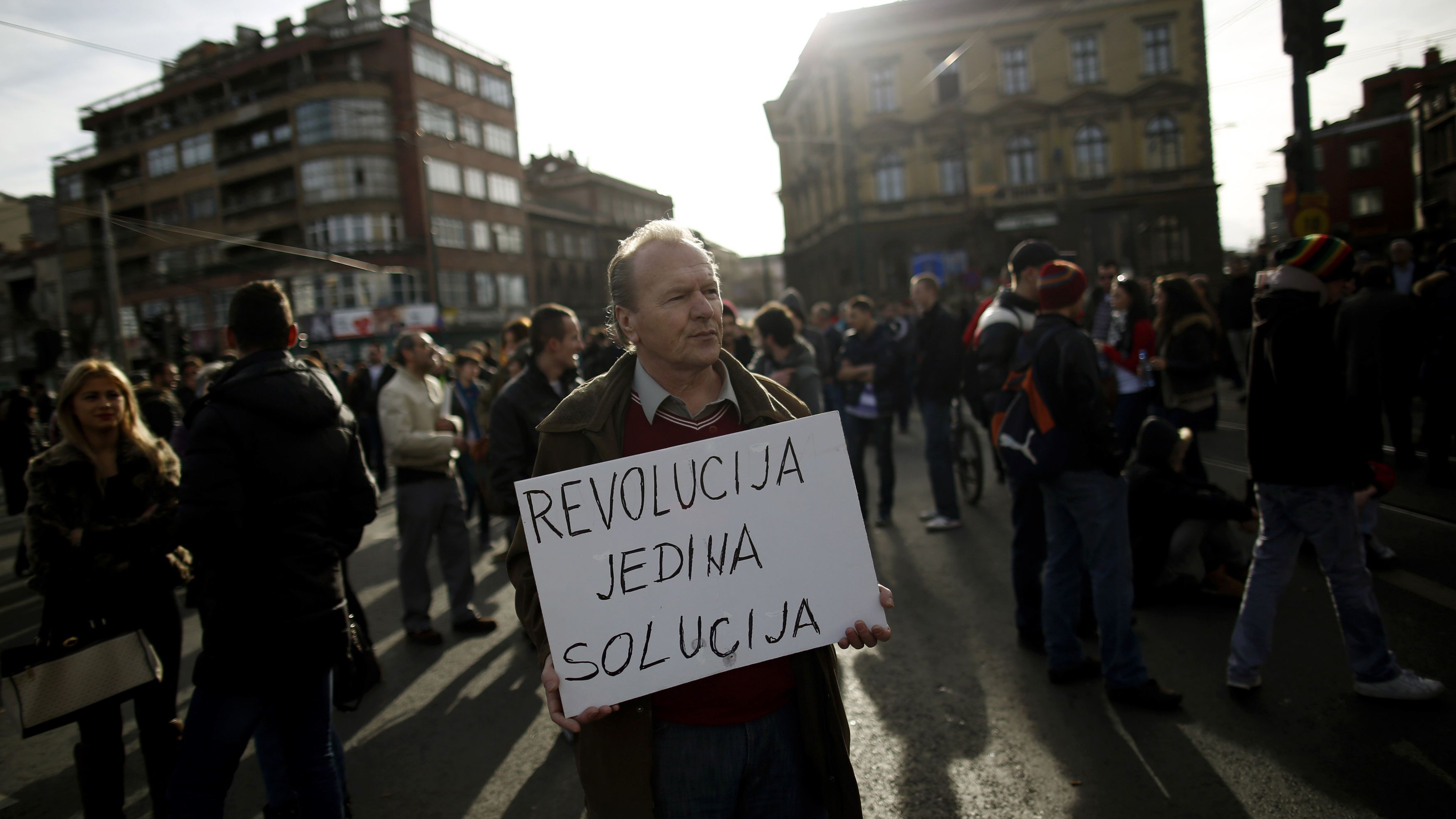 """An anti-government protester holds a placard that reads """"Revolution is the only solution"""" as protesters block Alipasina street during protests in Sarajevo in Feb. 2014"""