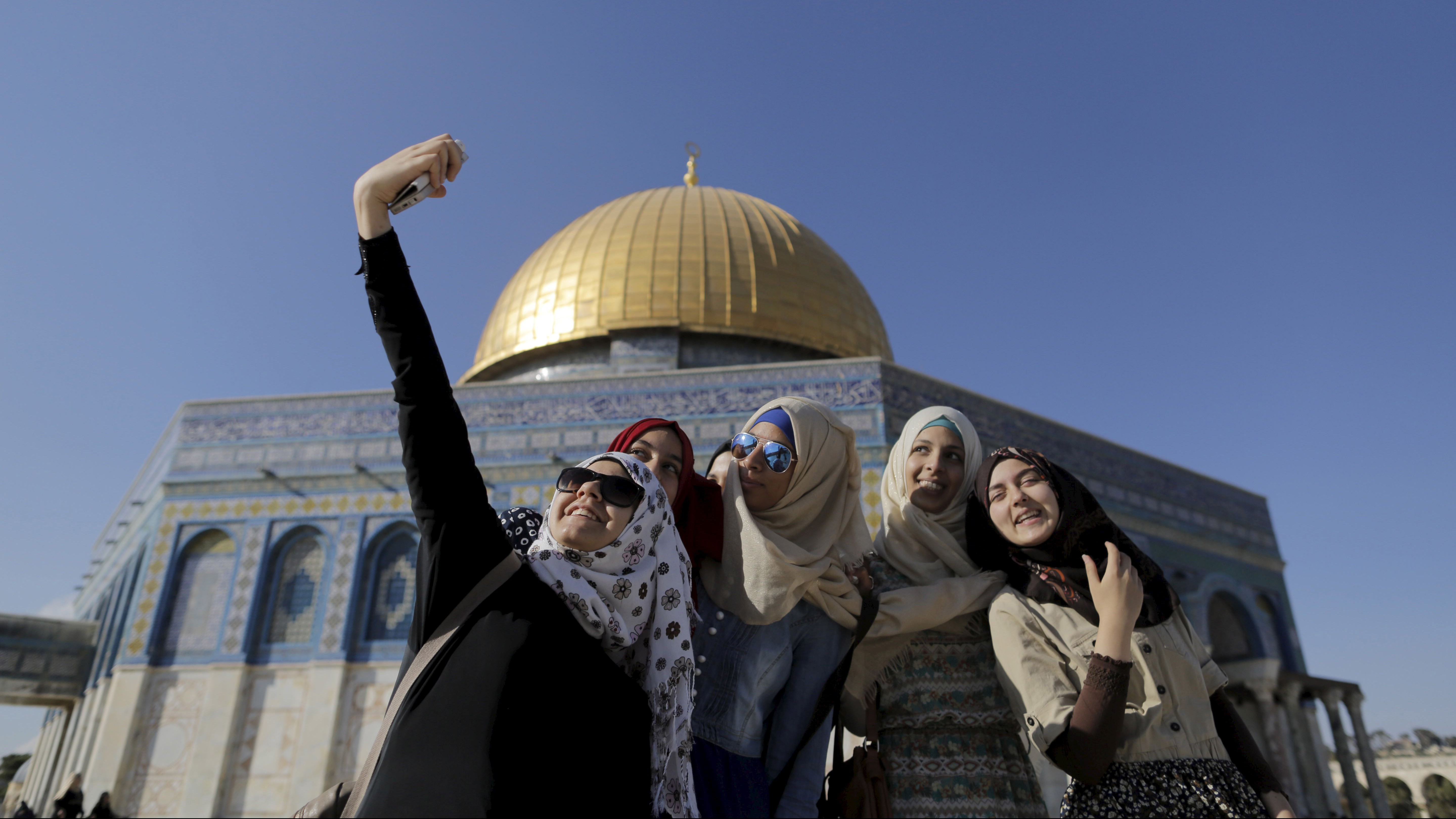 Palestinian Sanaa Abu Jaudi (L), 16, from the West Bank city of Jenin, takes a selfie photo with friends in front of the Dome of the Rock