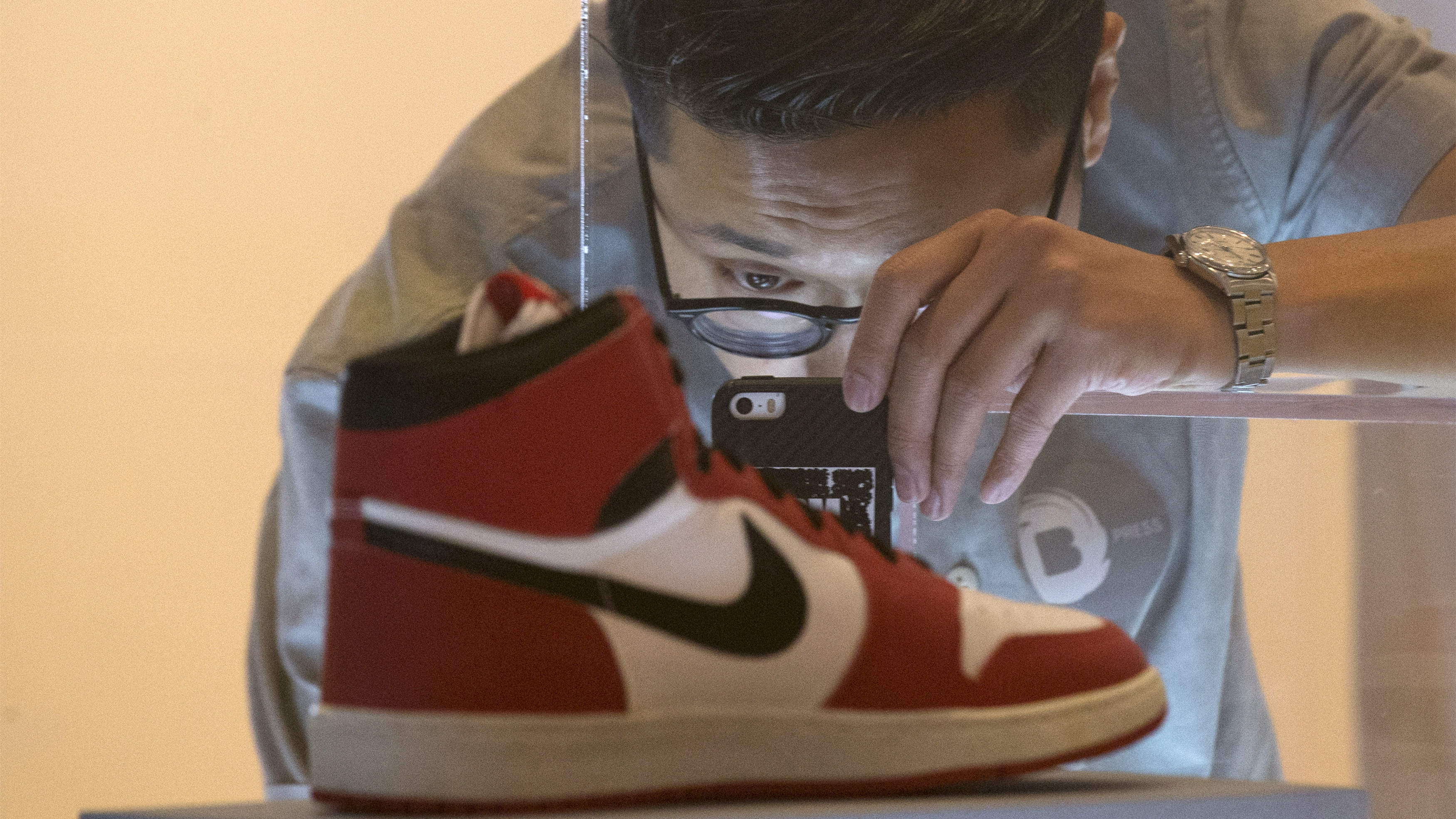 A visitor photographs an Air Jordan I during a preview for