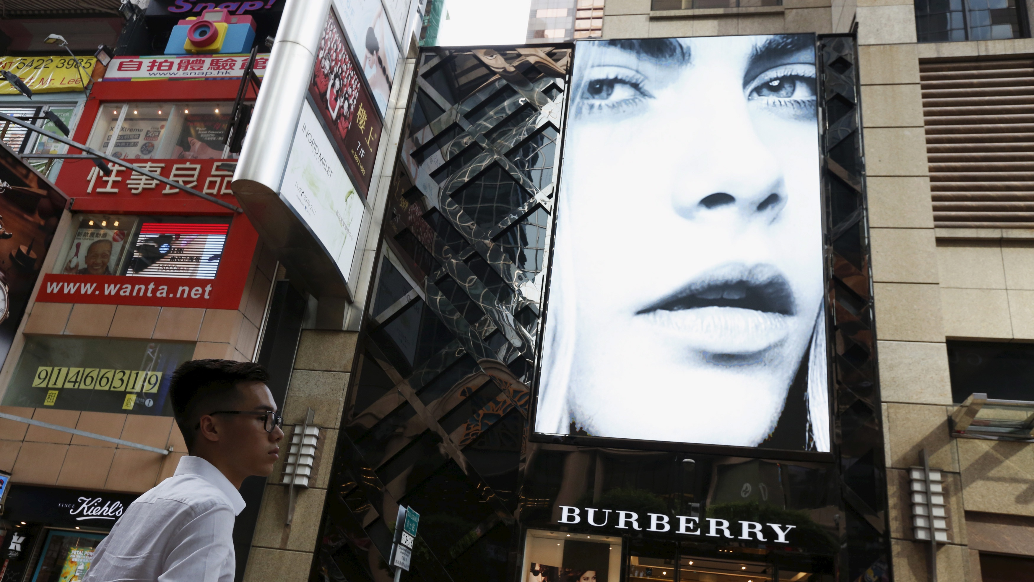 A model is seen on the screen of a Burberry store at Causeway Bay shopping district in Hong Kong, China, July 16, 2015. British luxury goods maker Burberry says its Hong Kong comparable store sales fell by a double-digit percentage in the quarter ending June 30, becoming the latest brand to show business is hurting.