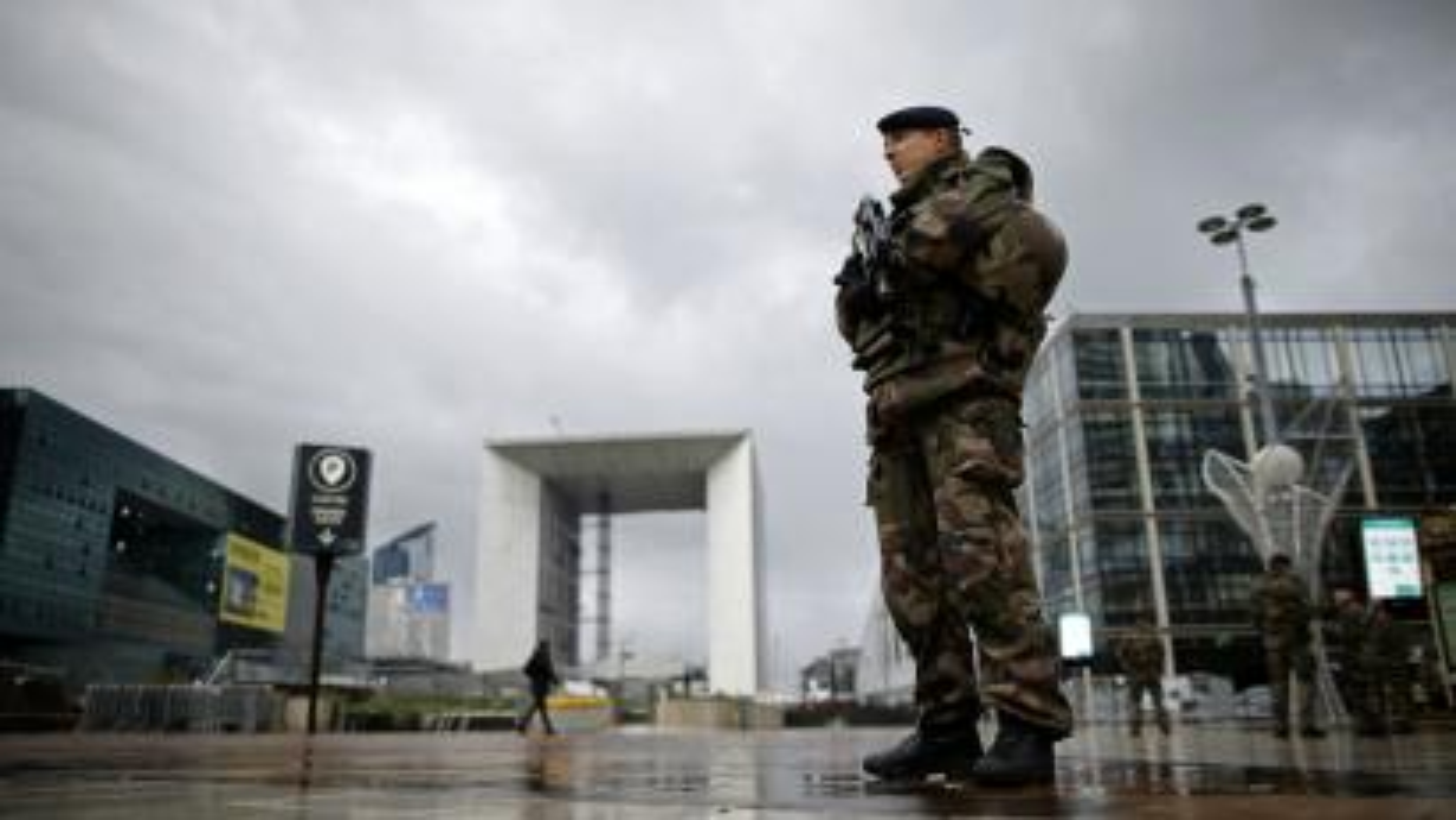 A French soldier patrols near the Arche de la Defense at La Defense business district near Paris, France, November 25, 2015.