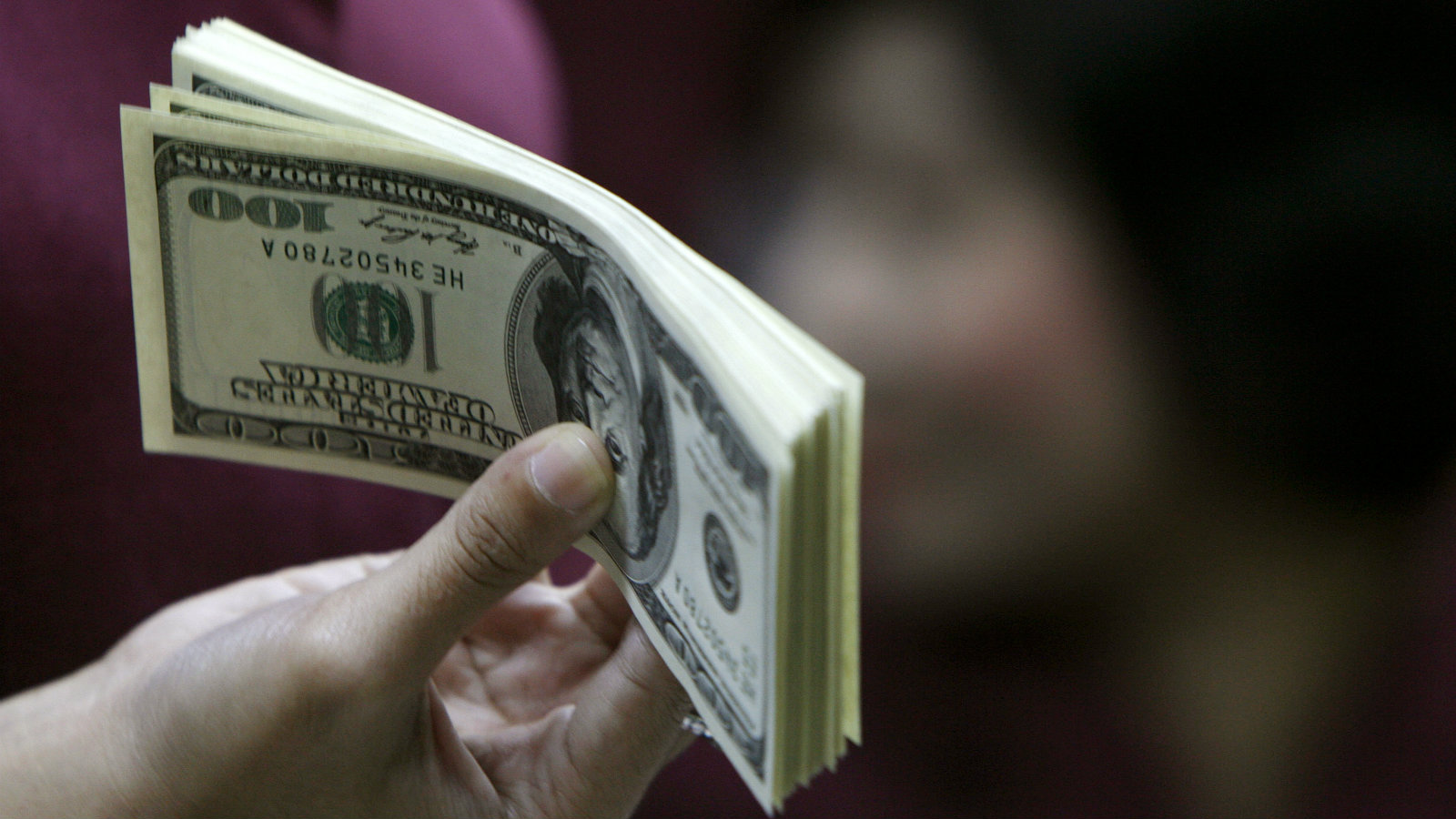 An employee working as a money changer prepares U.S. dollar currency for a customer in Jakarta October 28, 2008. The Indonesian rupiah tumbled in offshore forward markets as investors positioned themselves for further weakness in the high-yielding currency.