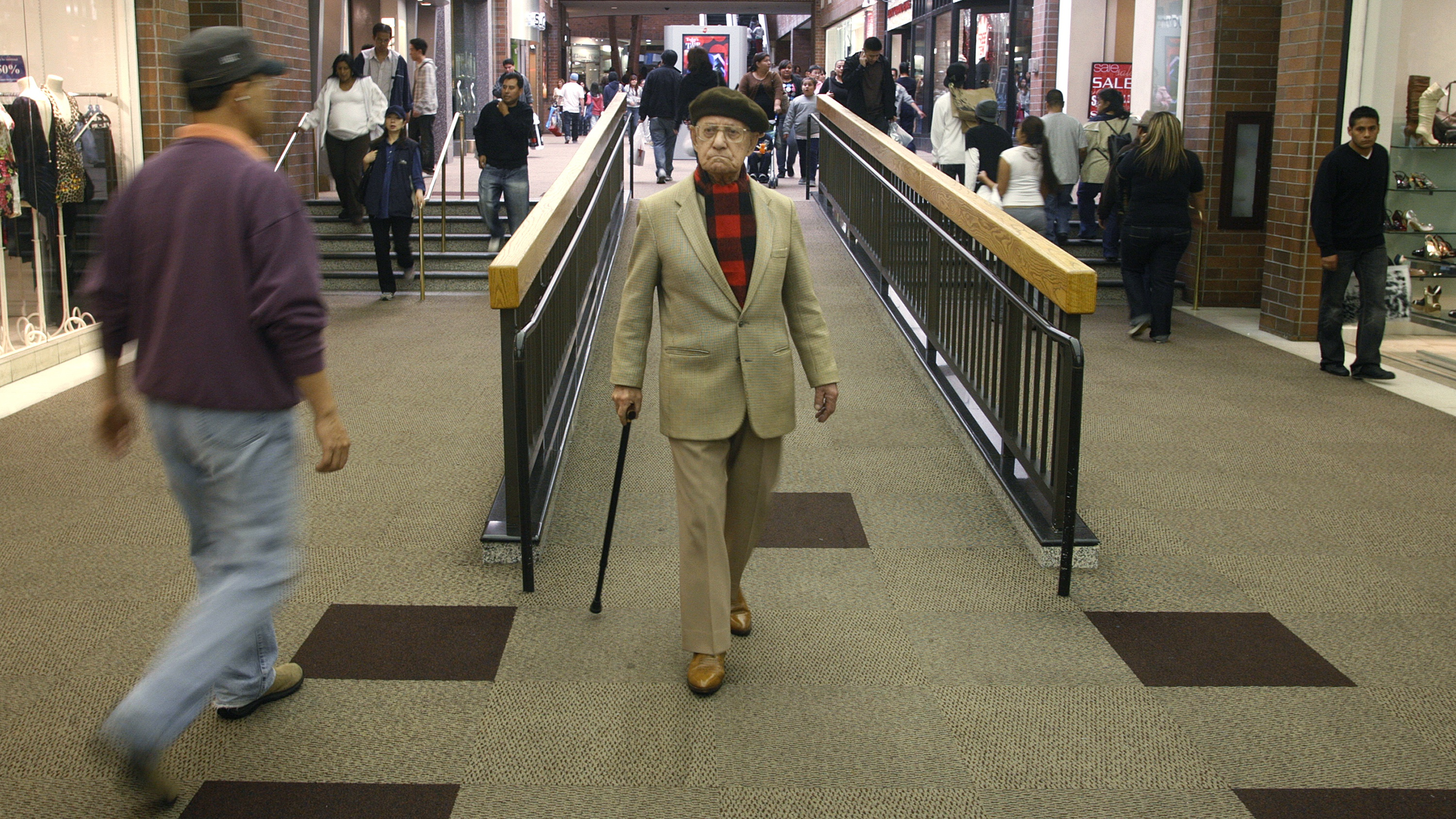 An elderly man walks with his cane amid shoppers at the Glendale Galleria shopping mall on Black Friday in Glendale, California November 28, 2008.
