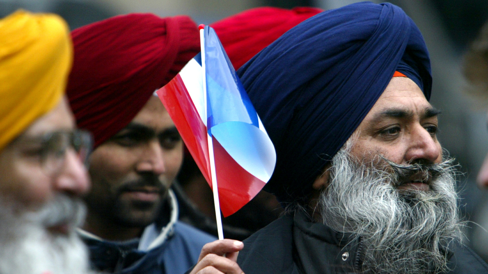 Sikhs wave the french national flag as about 3,000 Sikhs from across Europe march on a Paris boulevard to defend their traditional headgear against a looming French ban on religious symbols in state schools, Paris January 31, 2004. Sikhs say turbans and the light scarves that [women] wear are not religious but practical items meant to cover the hair they never cut.