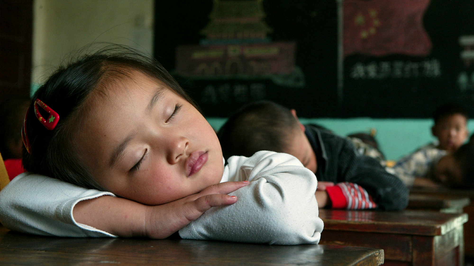 Chinese school children sleep at their desks during a noon break at a private elementary school for .....