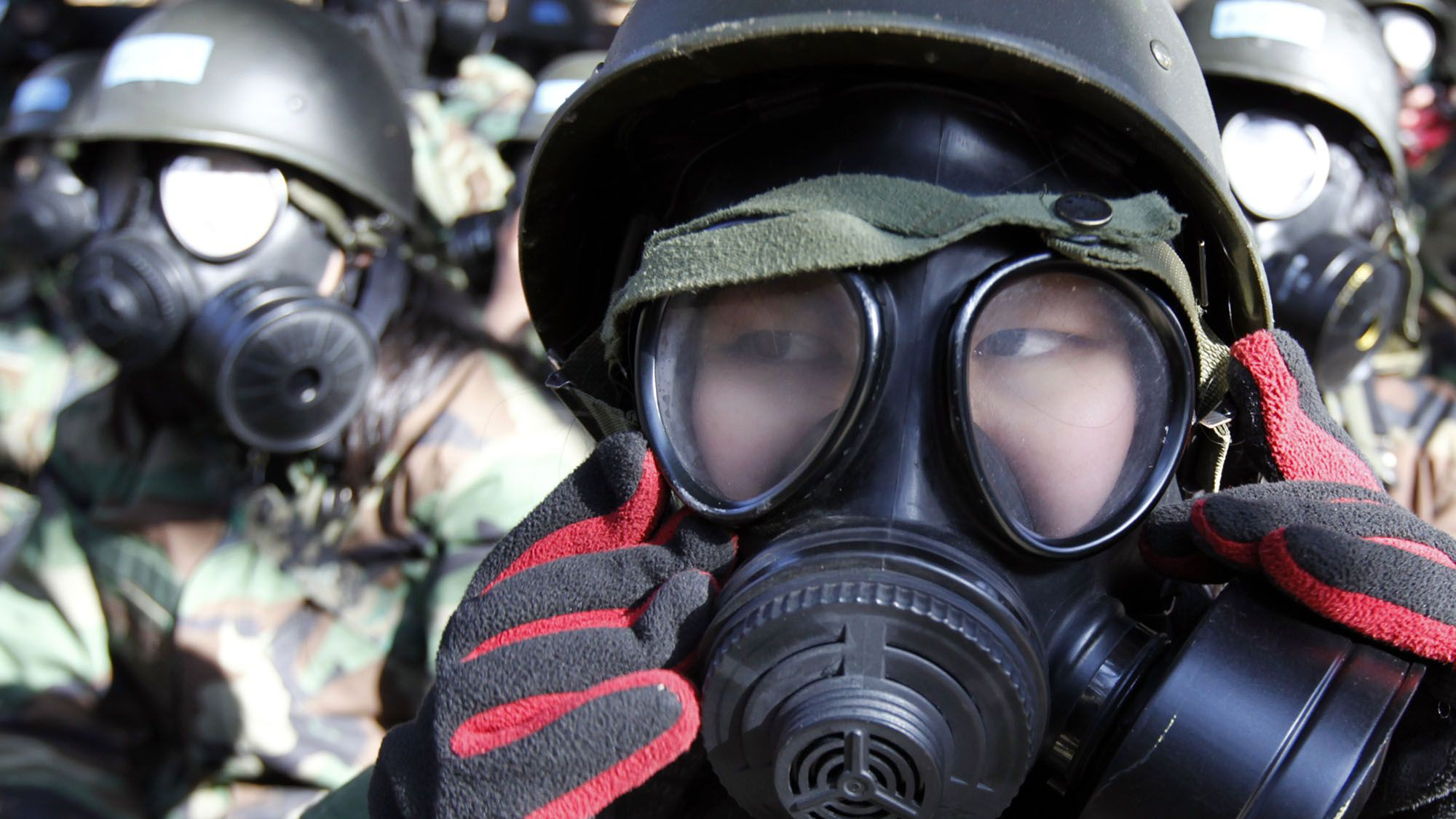 Students wear gasmasks before entering a building where they will be exposed to tear gas as part of their chemical, biological and radiological training during a winter military boot camp at a military unit in Bucheon, west of Seoul January 20, 2011. The boot camp is run by South Korean special forces, who have organised six winter boot camps across the country in January. There are currently 1,200 civilians including students, who participate in the four-day long boot camp.