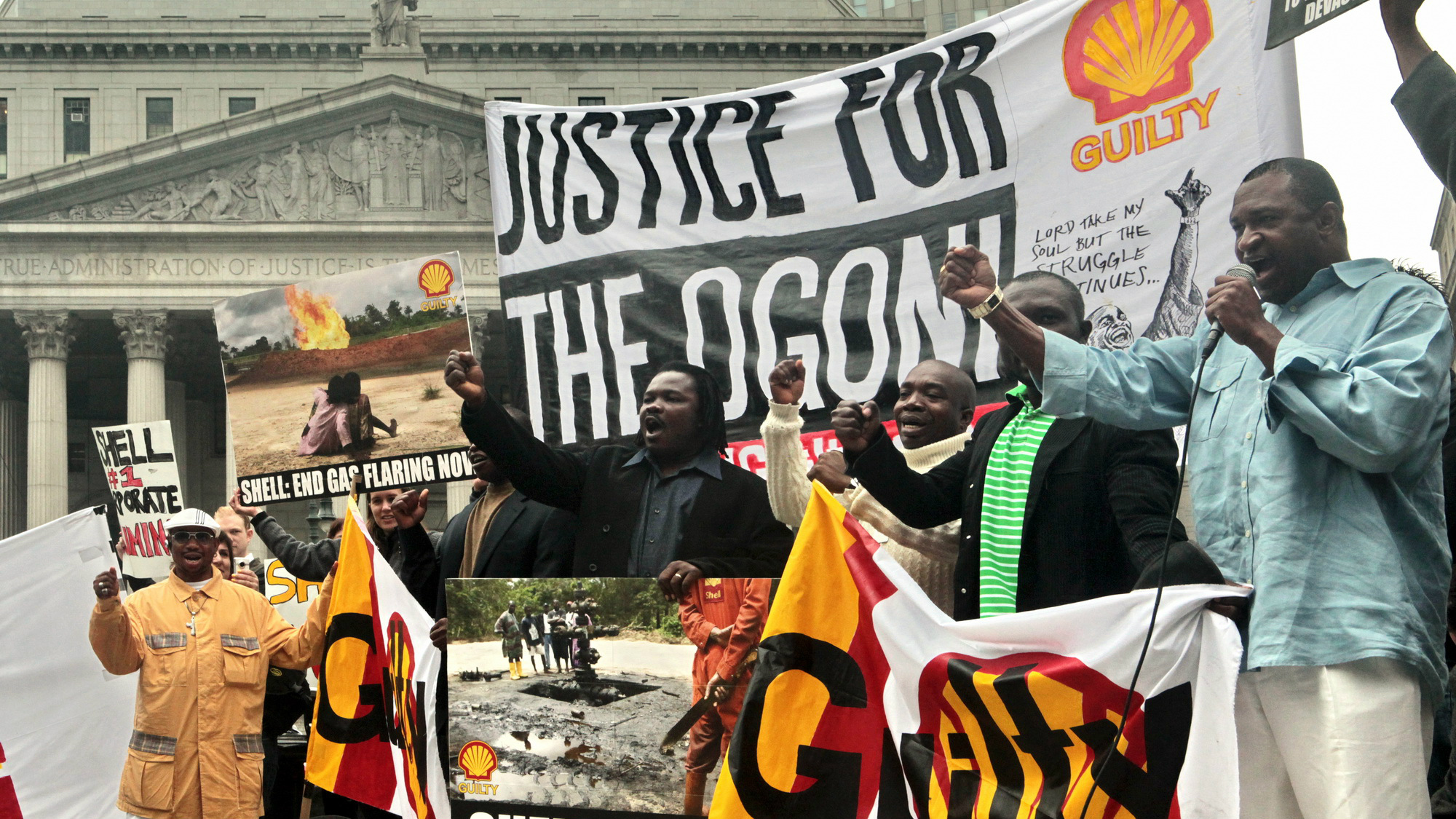 """Ben Wulloo Ikari, far right, a member of Nigeria's Ogoni community, leads a rally to raise awareness of the upcoming New York trial of the Royal Dutch Shell oil company charged with complicity in the death of countryman Ken Saro-Wiwa and human rights abuses in Nigeria, New York, Wednesday May 27, 2009. Ikari, who worked as a human rights activist with Saro-Wiwa and was granted political asylum to the U.S. in 1995 following his death, shared the expectation that Shell """"will finally answer for its role in atrocities committed against the Ogoni people of Nigeria."""" (AP Photo/Bebeto Matthews)"""